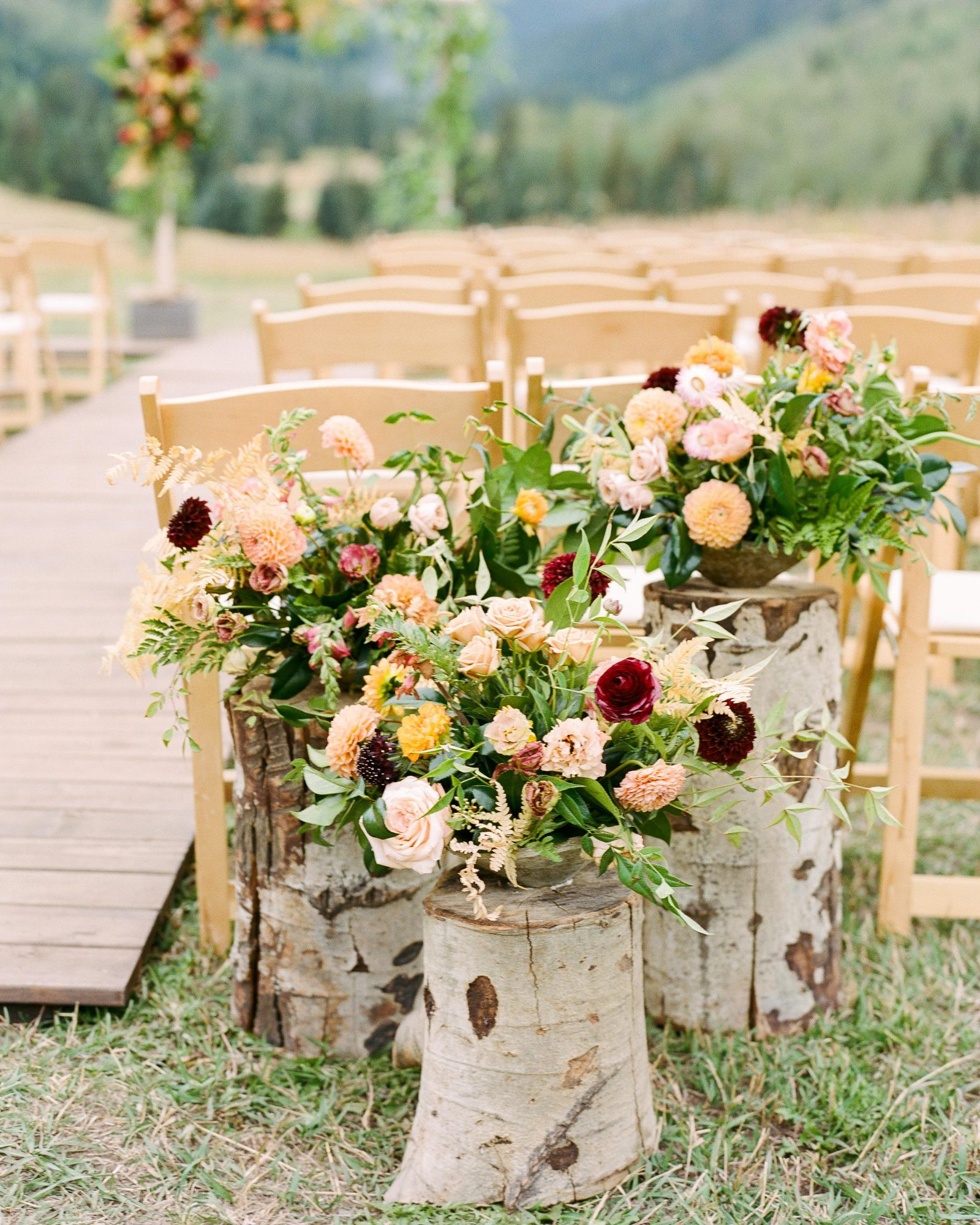 jill phil wedding outdoor ceremony decor featuring flowers and logs