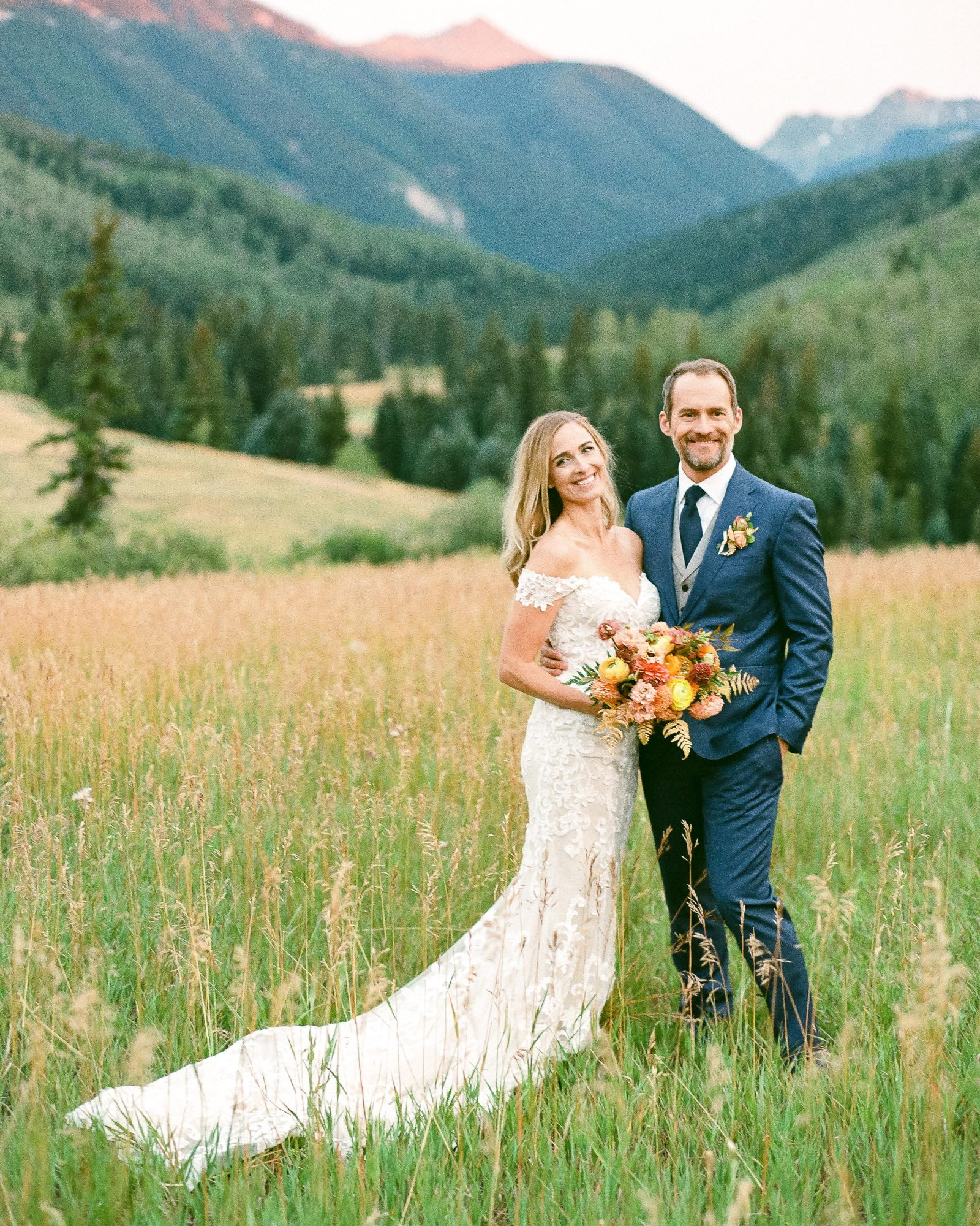 jill phil wedding couple posing in grass field with mountain view