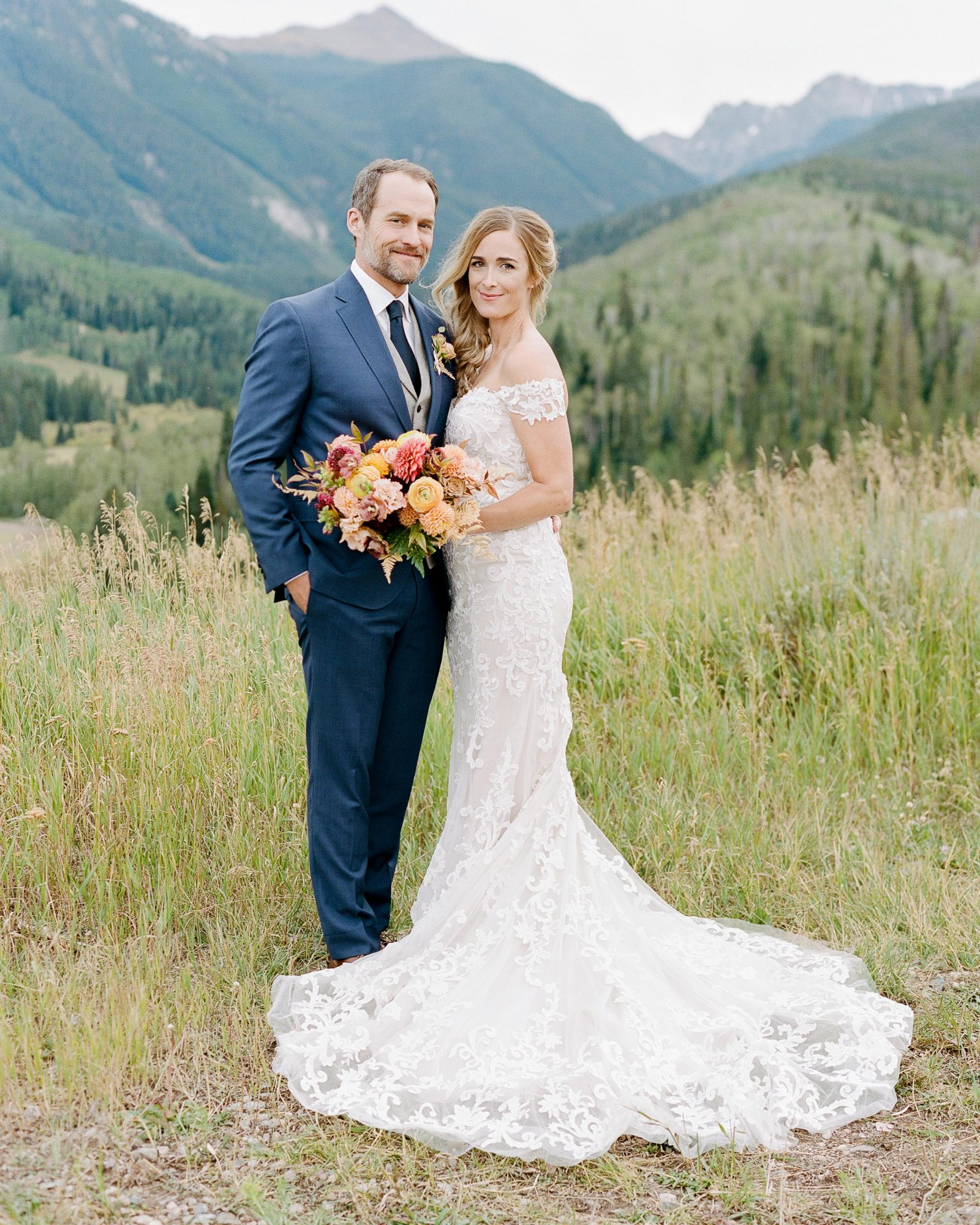 jill phil wedding couple pose surrounded by greenery and a mountain view