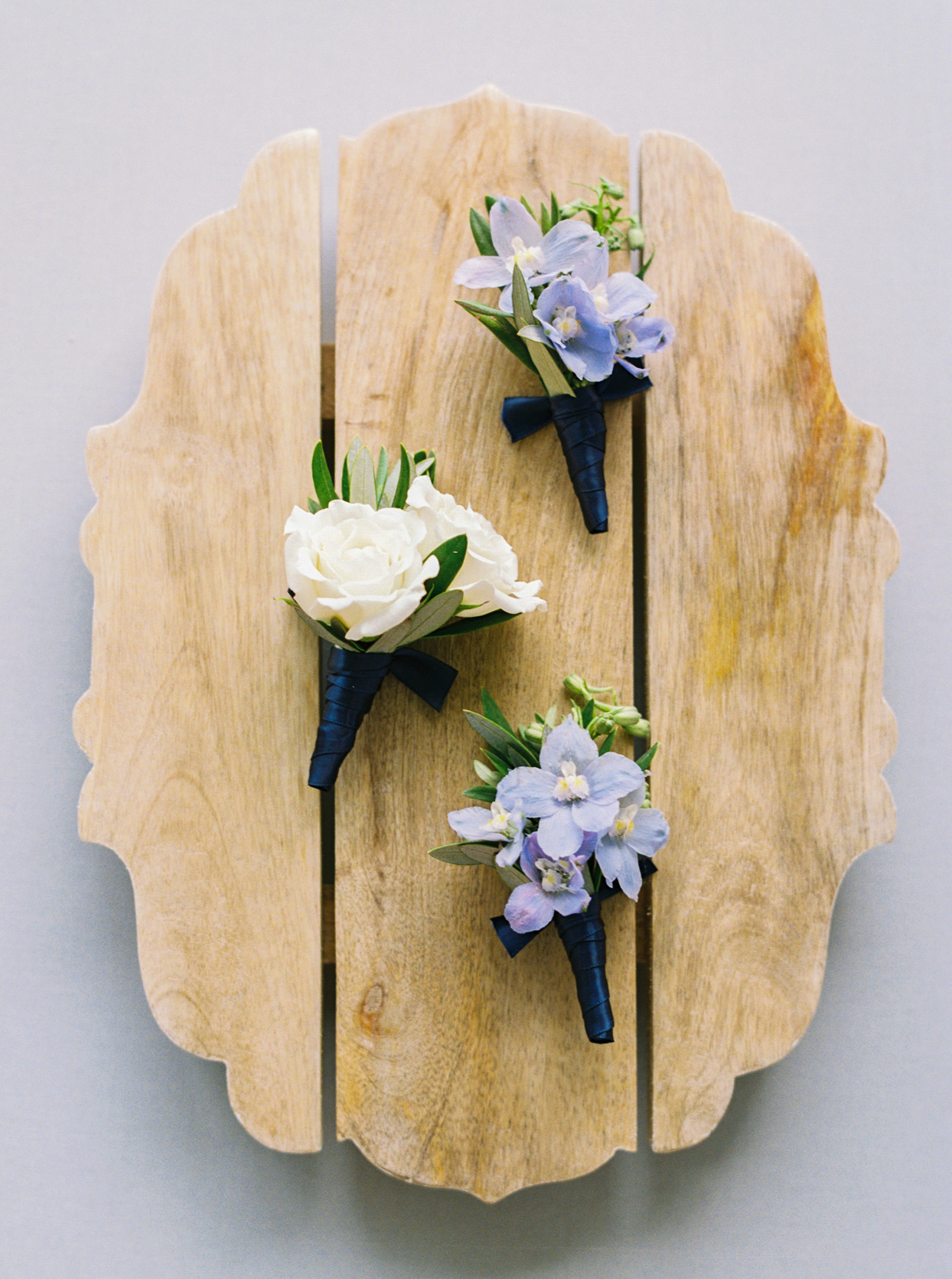 blue, white, and green floral boutonnieres on wooden display