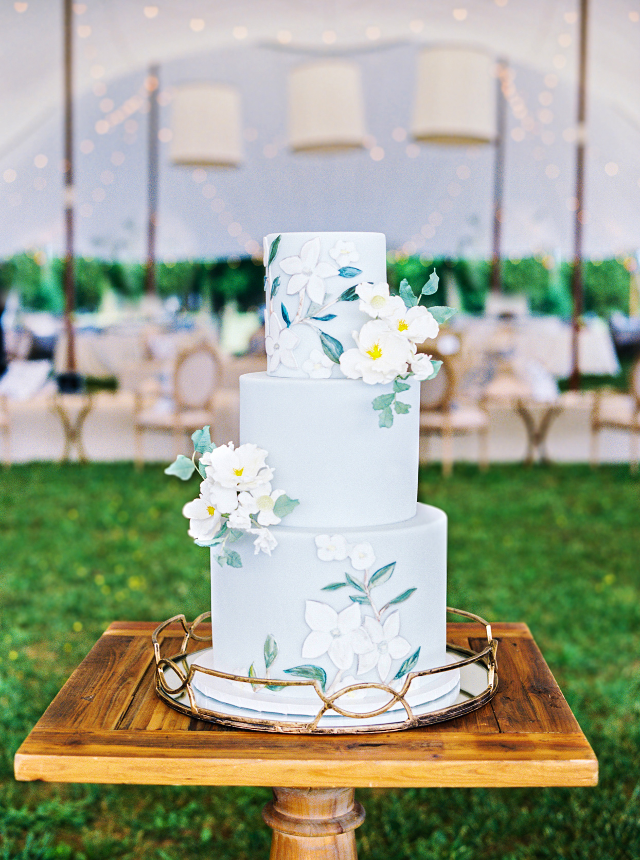 three tiered pale blue frosted floral design wedding cake on wooden stand