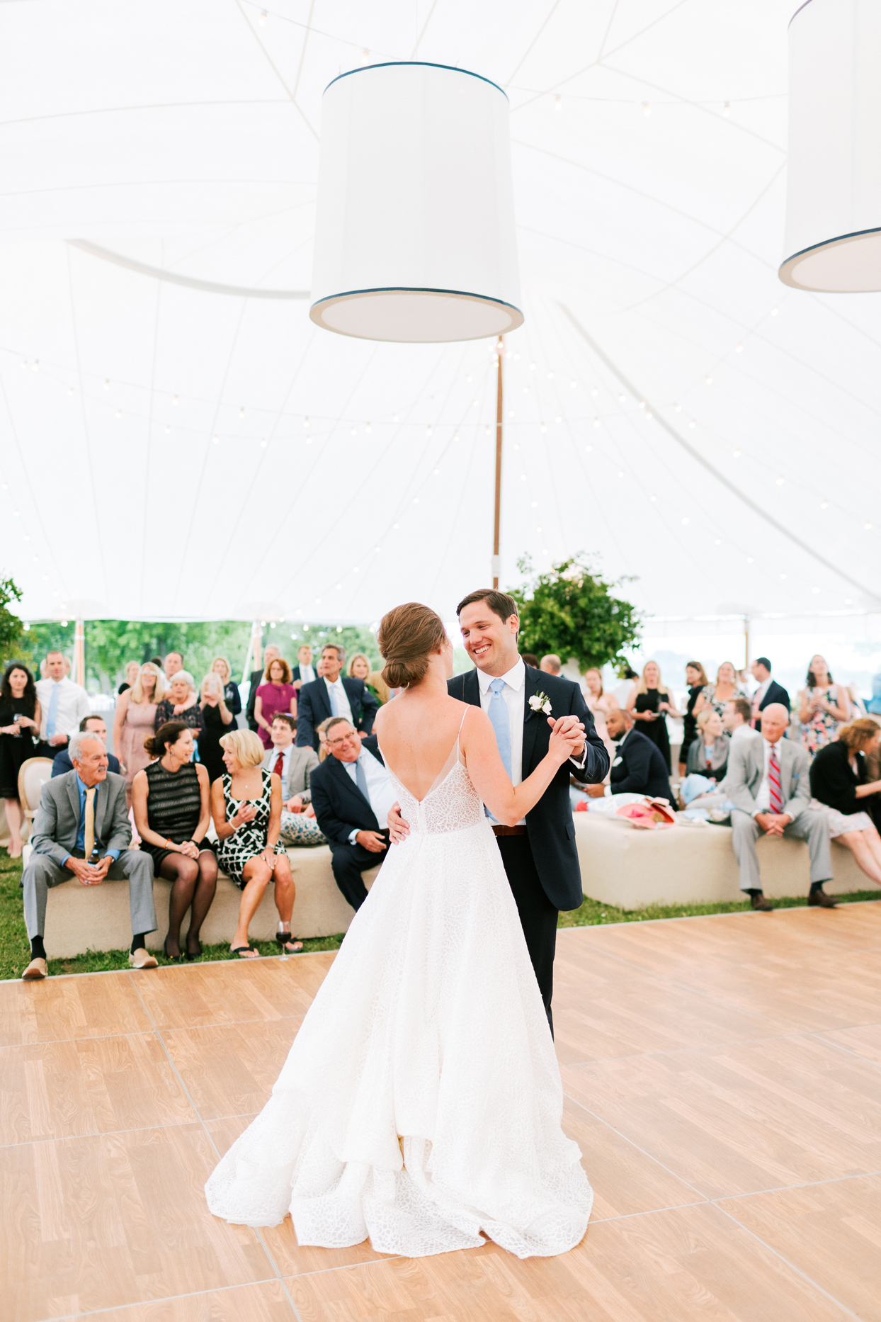 bride and groom first dance on dance floor under large white reception tent