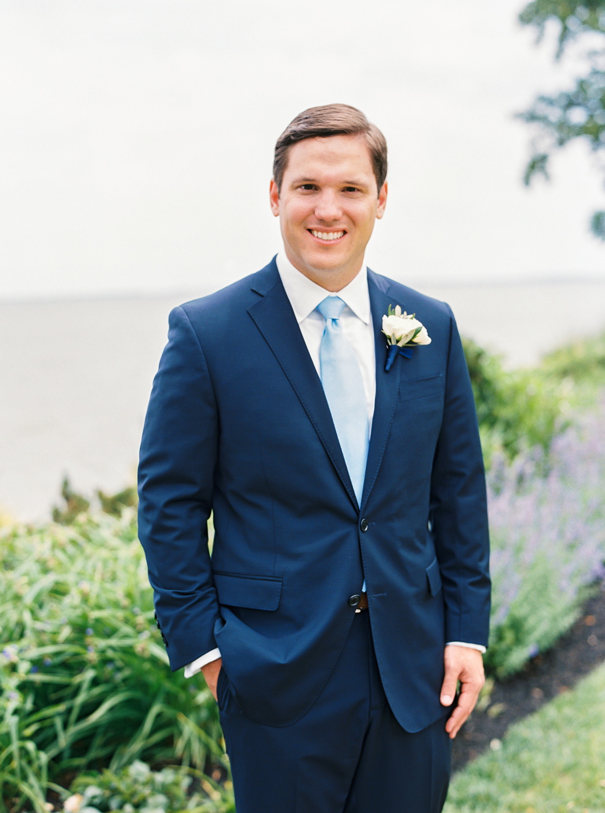 groom wearing navy blue suit with light blue tie and boutonniere