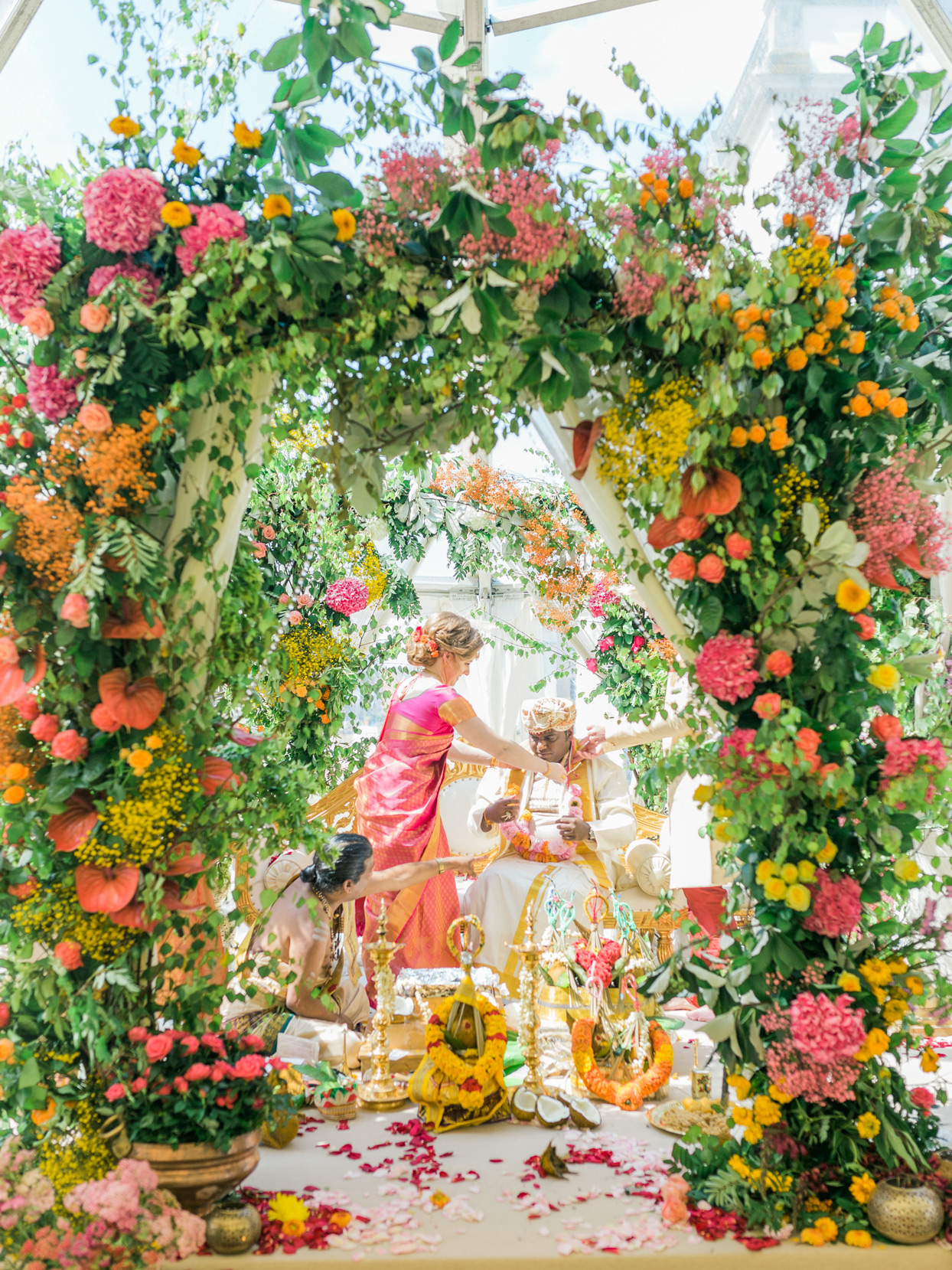 couple under Mandap decorated with greenery and pink, yellow, and orange flowers