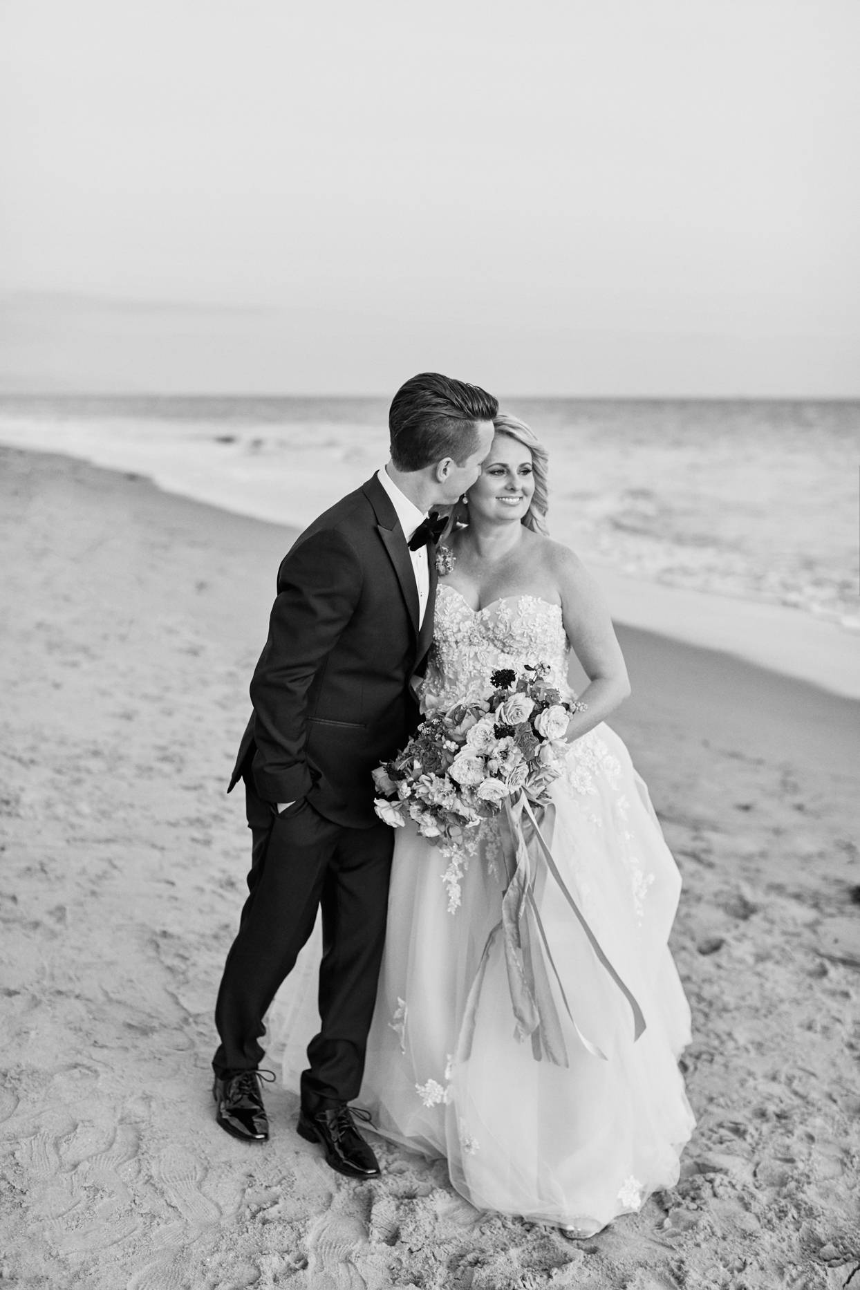 groom kisses bride on cheek while walking on the beach