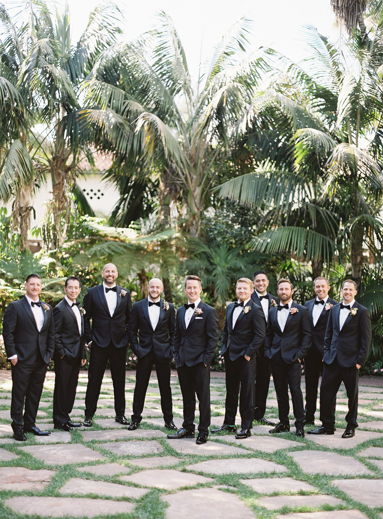 groom with nine groomsmen all wearing black tuxedos with bowties