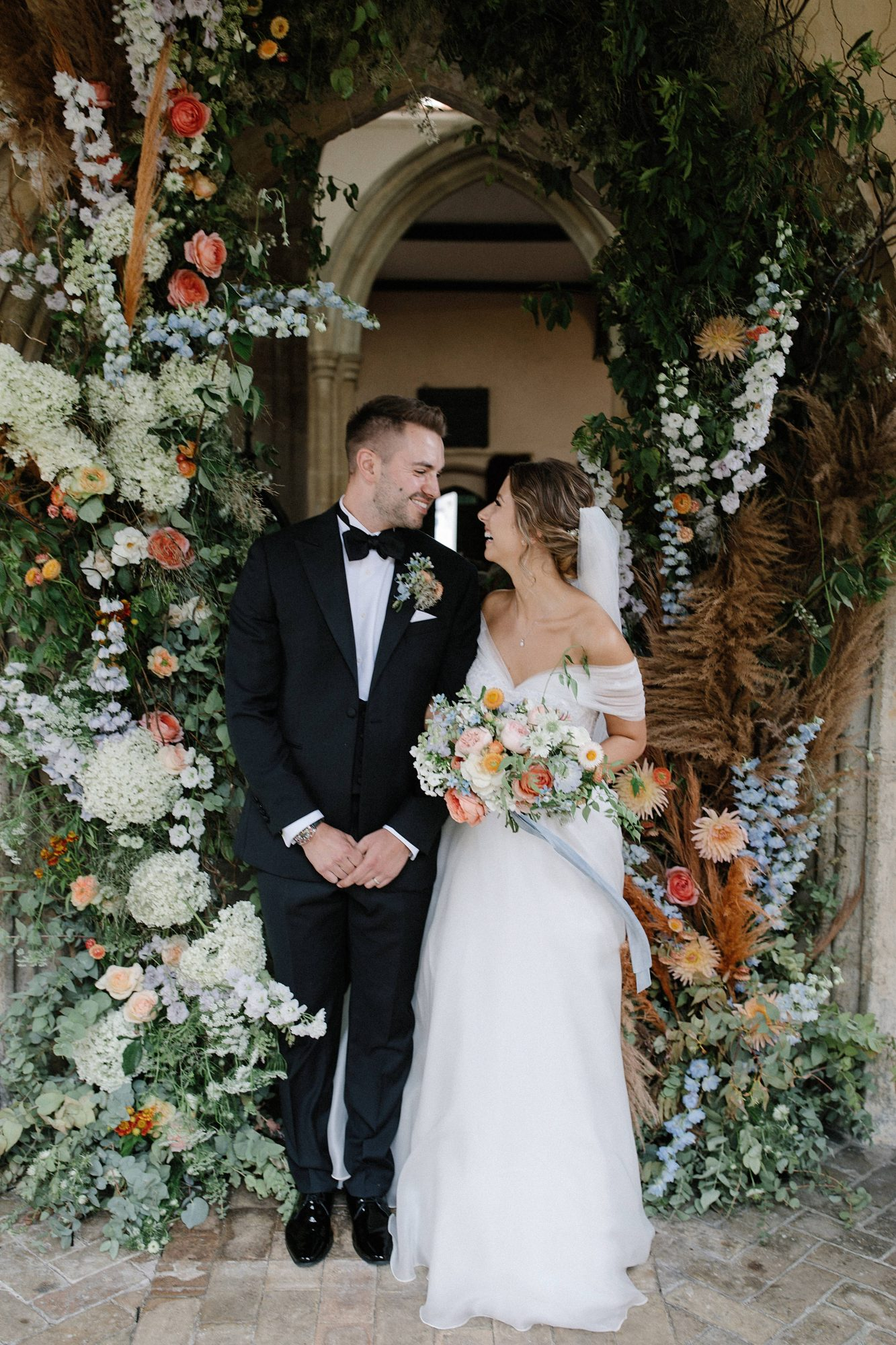 laurie lee wedding couple smiling under floral archway