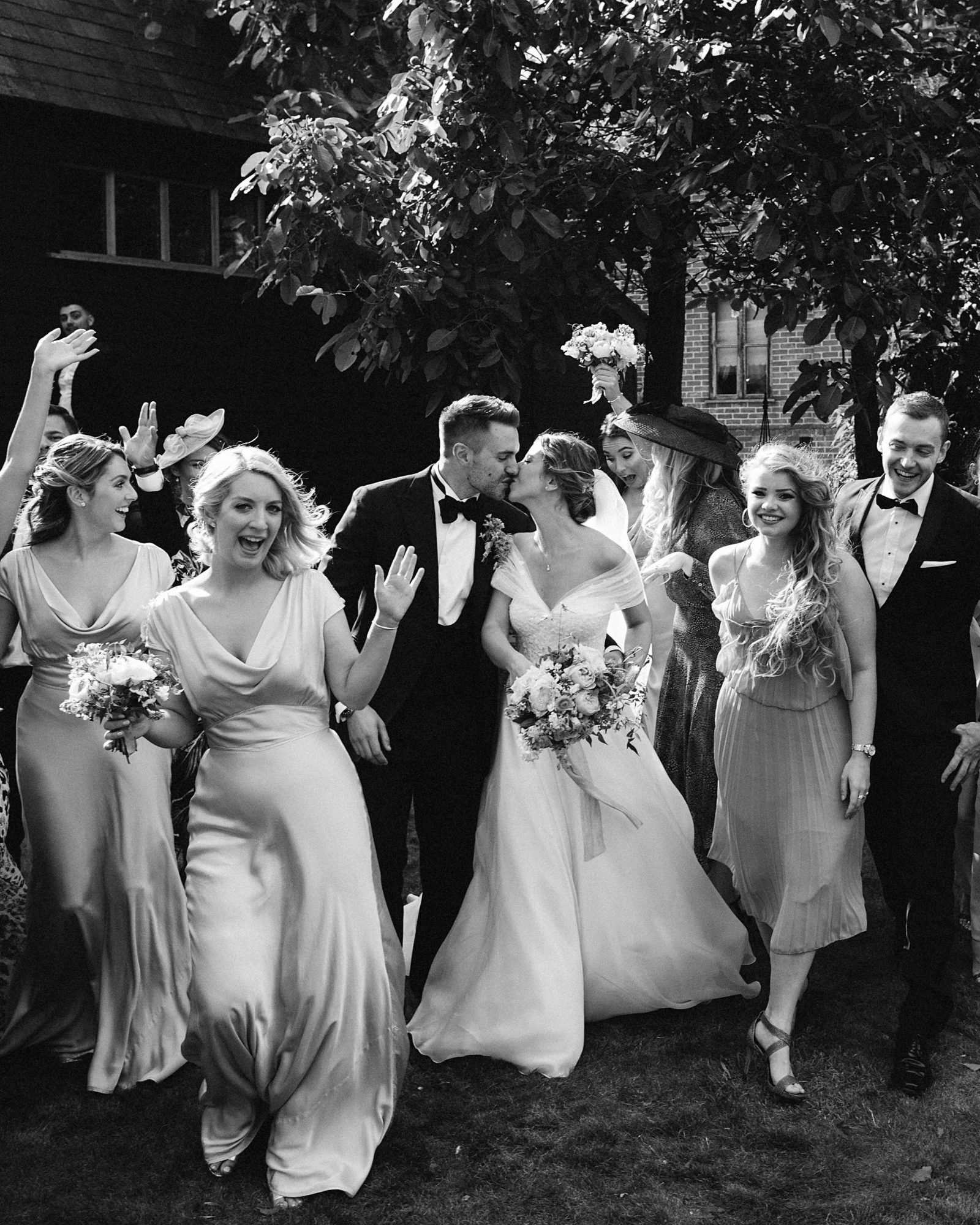 laurie lee wedding couple kiss surrounded by wedding party