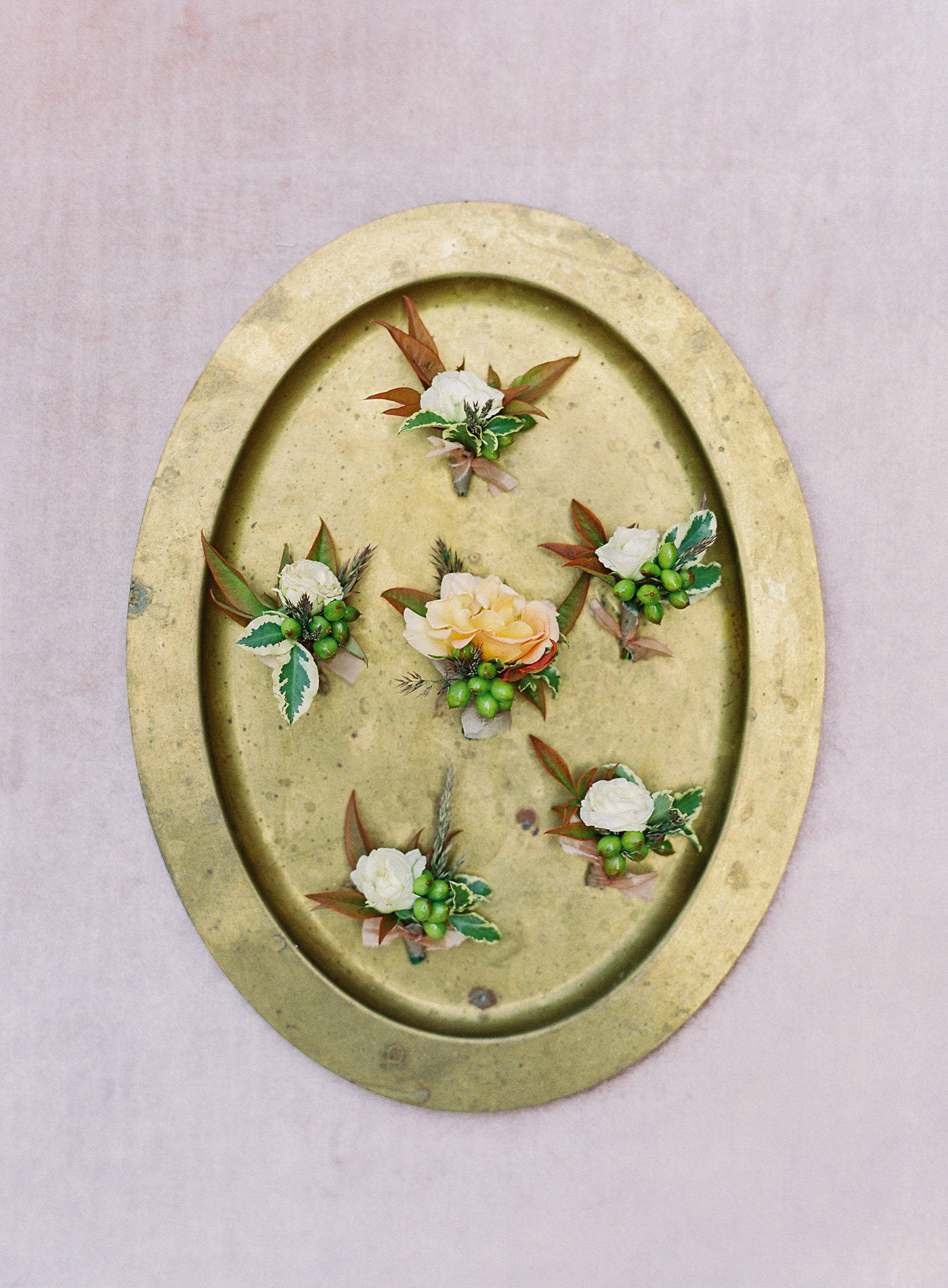 boutonnieres on gold oval platter