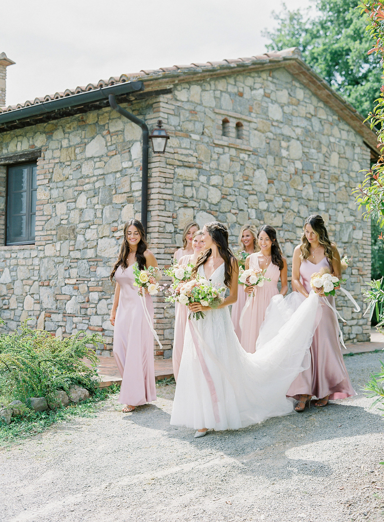 Madison with bridesmaids outside stone building