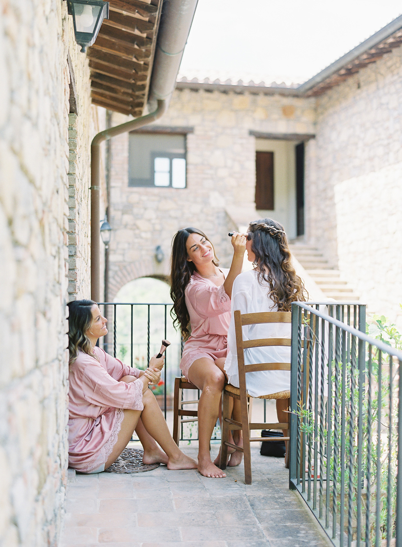 bridesmaid doing brides makeup outside balcony