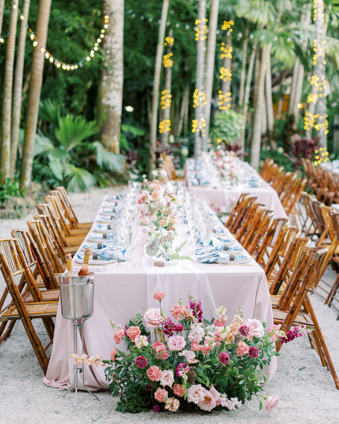 melissa lindsey wedding reception outdoor long table wooden chairs florals