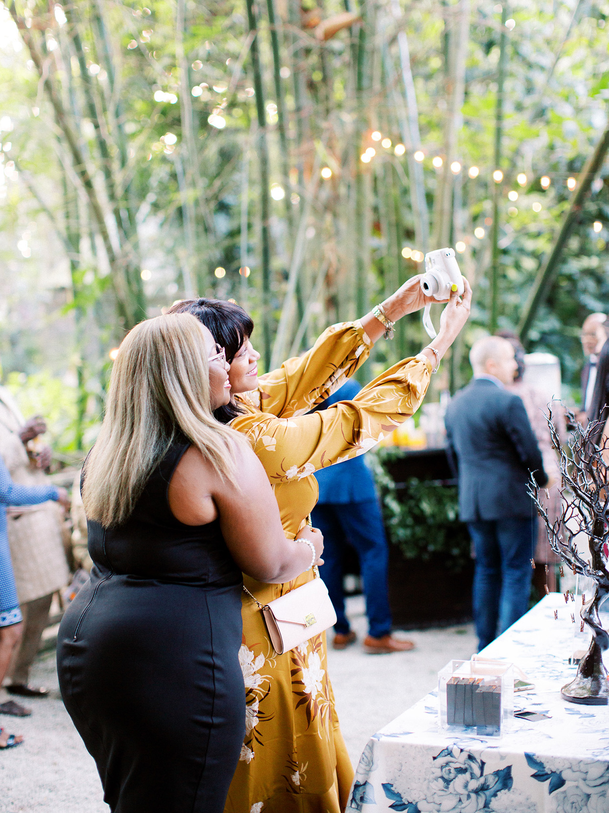 melissa lindsey wedding guests taking selfie with polaroid camera