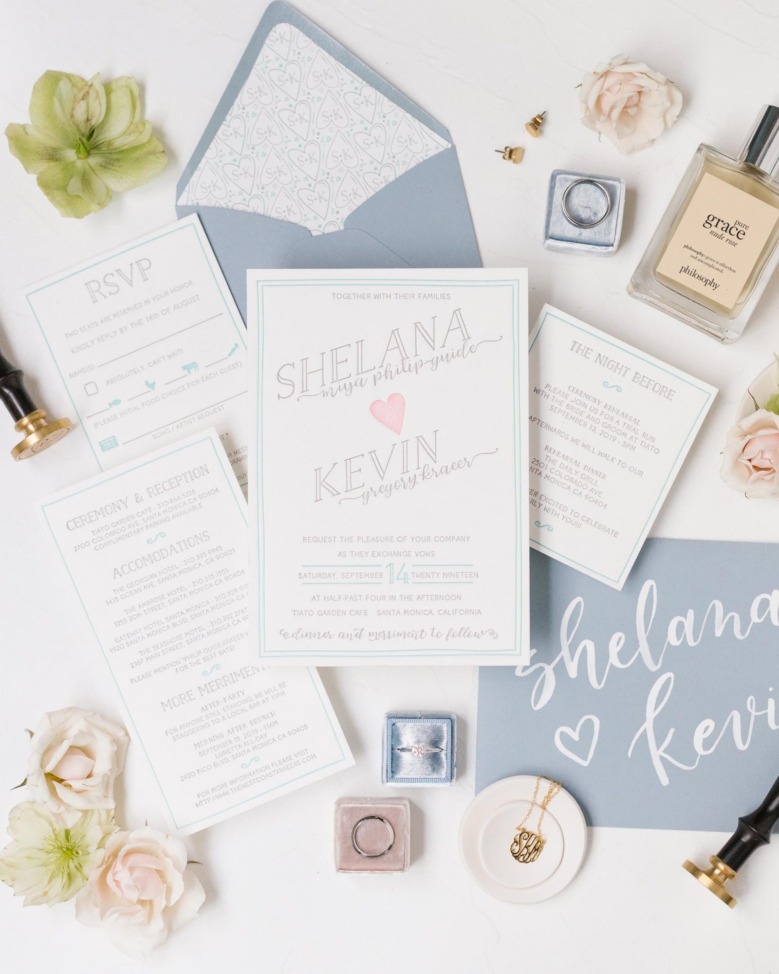 shelana kevin wedding invitation suite with blue detail surrounded by flowers