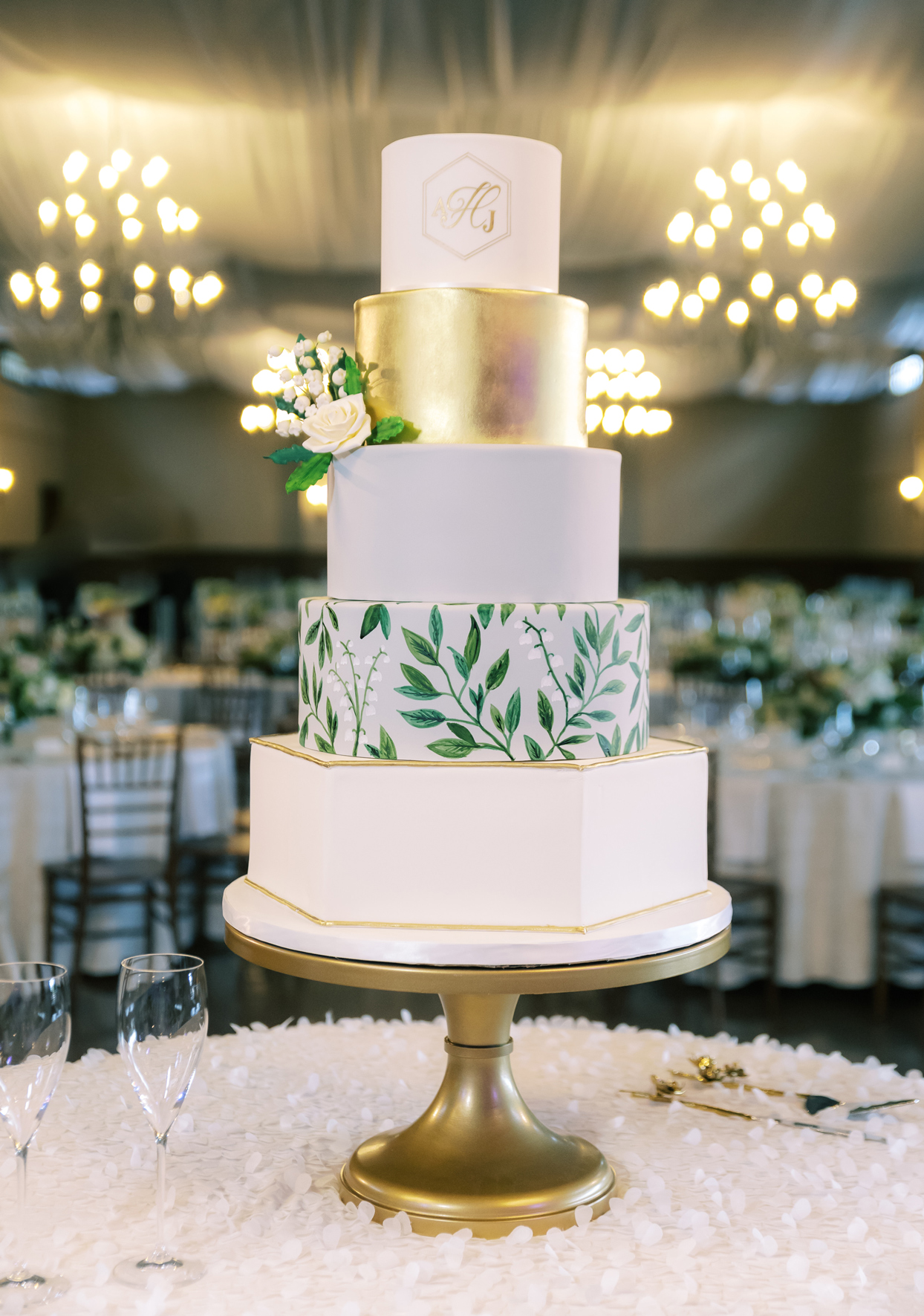 five tiered white and gold wedding cake with greenery accent