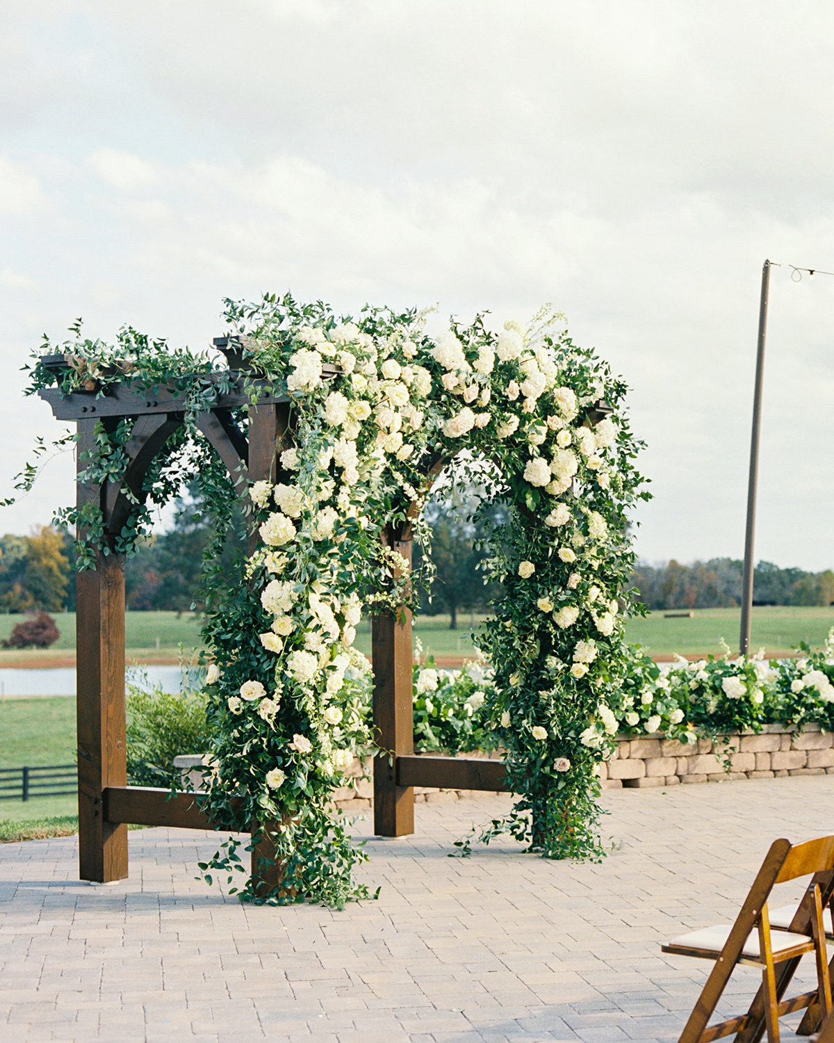 white floral and greenery wedding arch outside