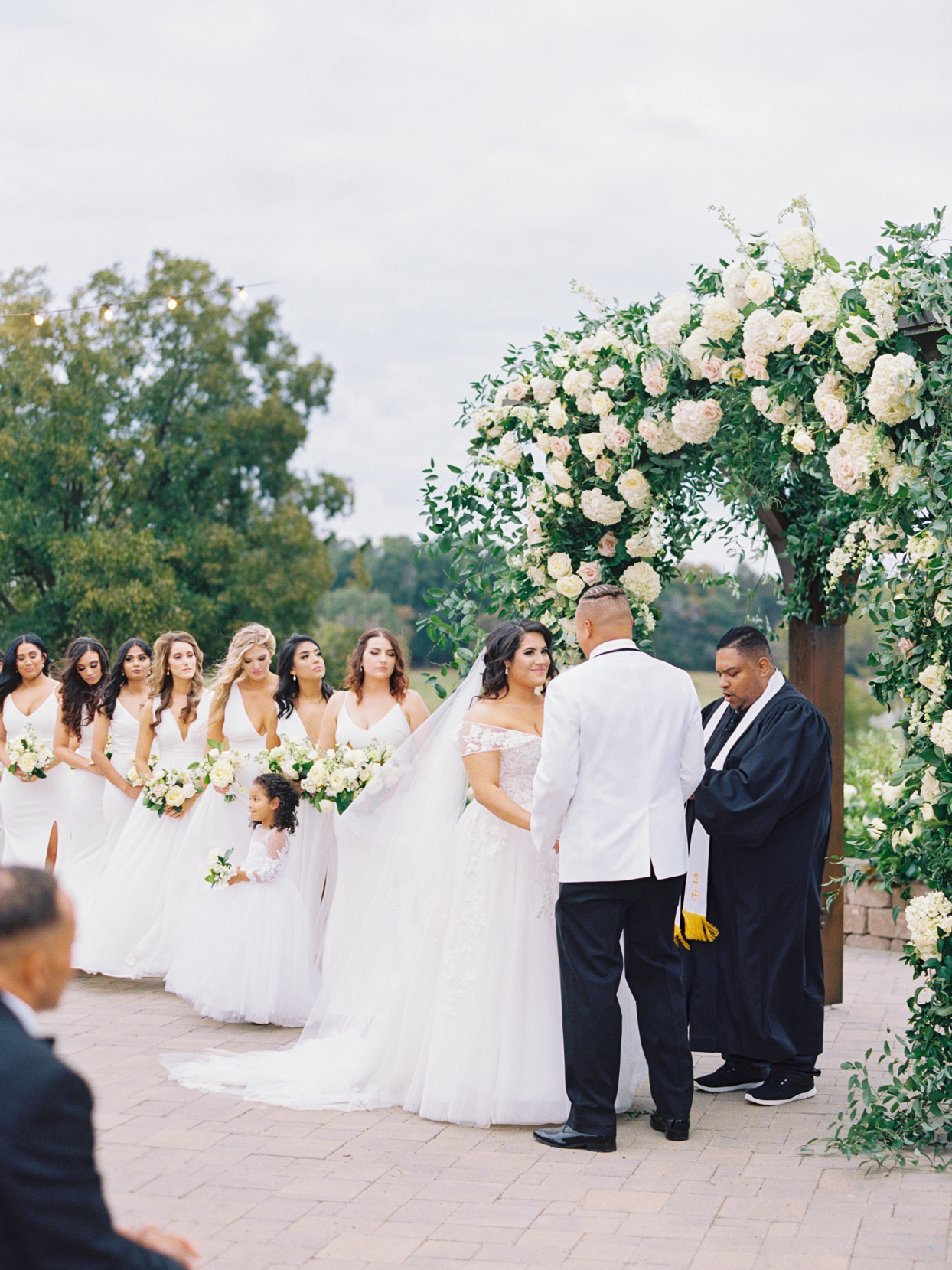 bride and groom under floral wedding arch during ceremony