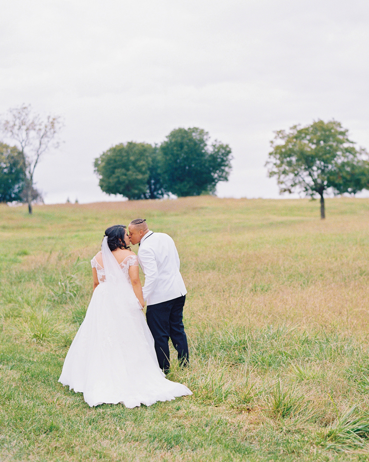 bride and groom kiss outside at farm wedding venue
