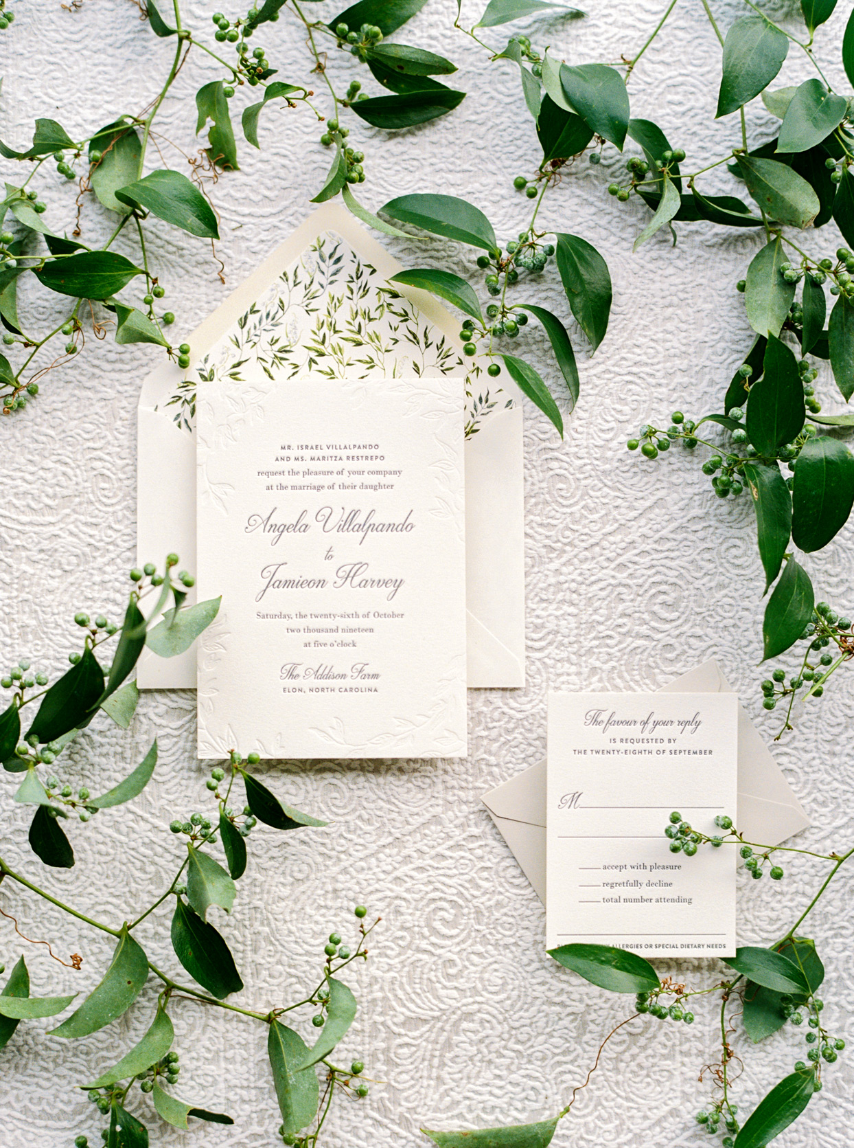 off-white wedding invites with greenery accents