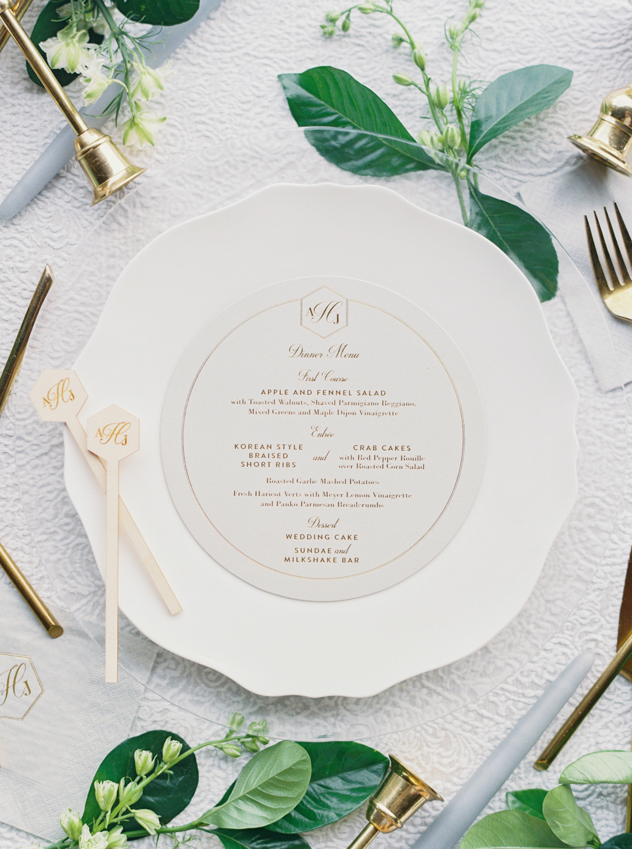 wedding reception menu with gold writing on white place setting with greenery accents