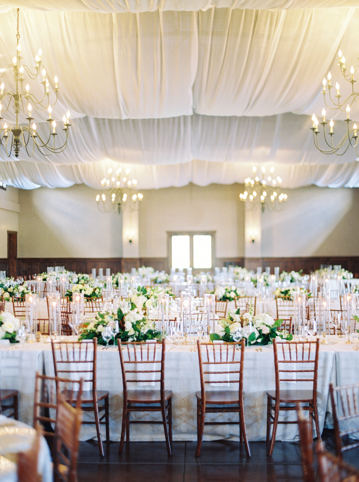 white linen covered wedding reception tables with wooden chairs indoor
