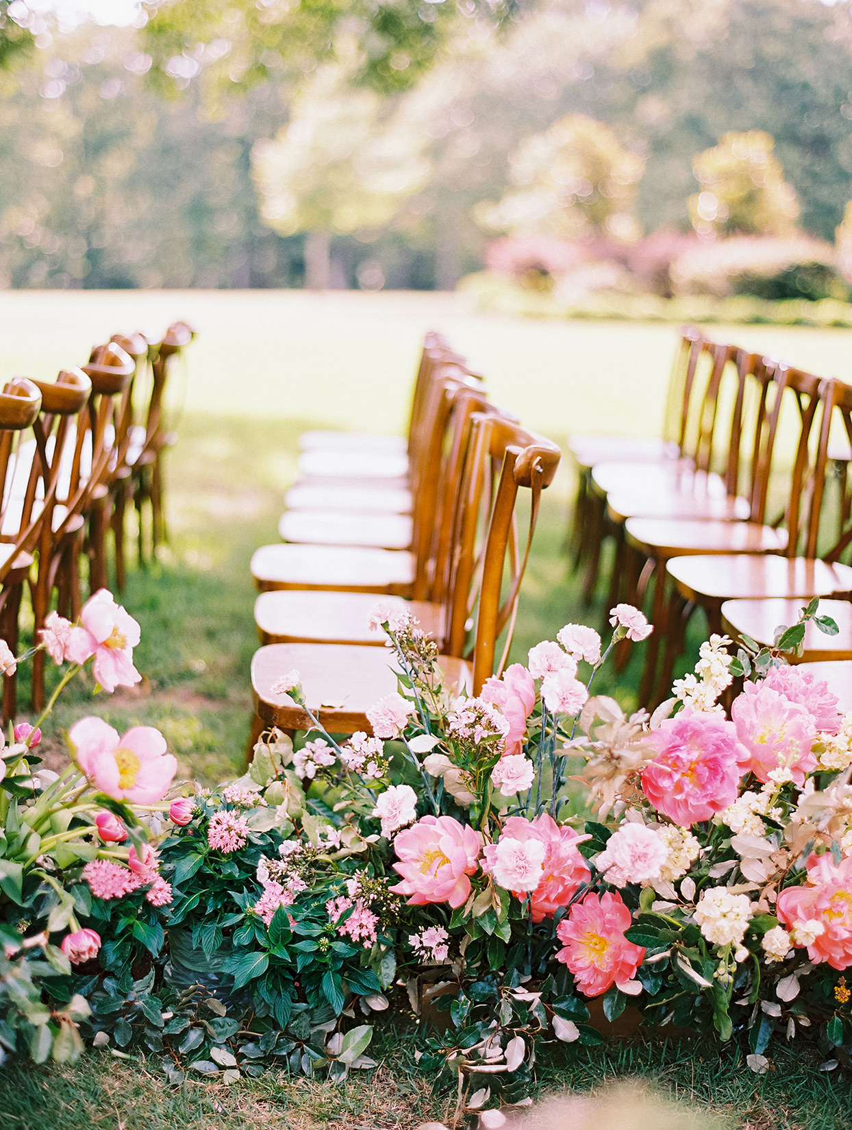 evie joe wedding outdoor ceremony aisle lined with pink flowers