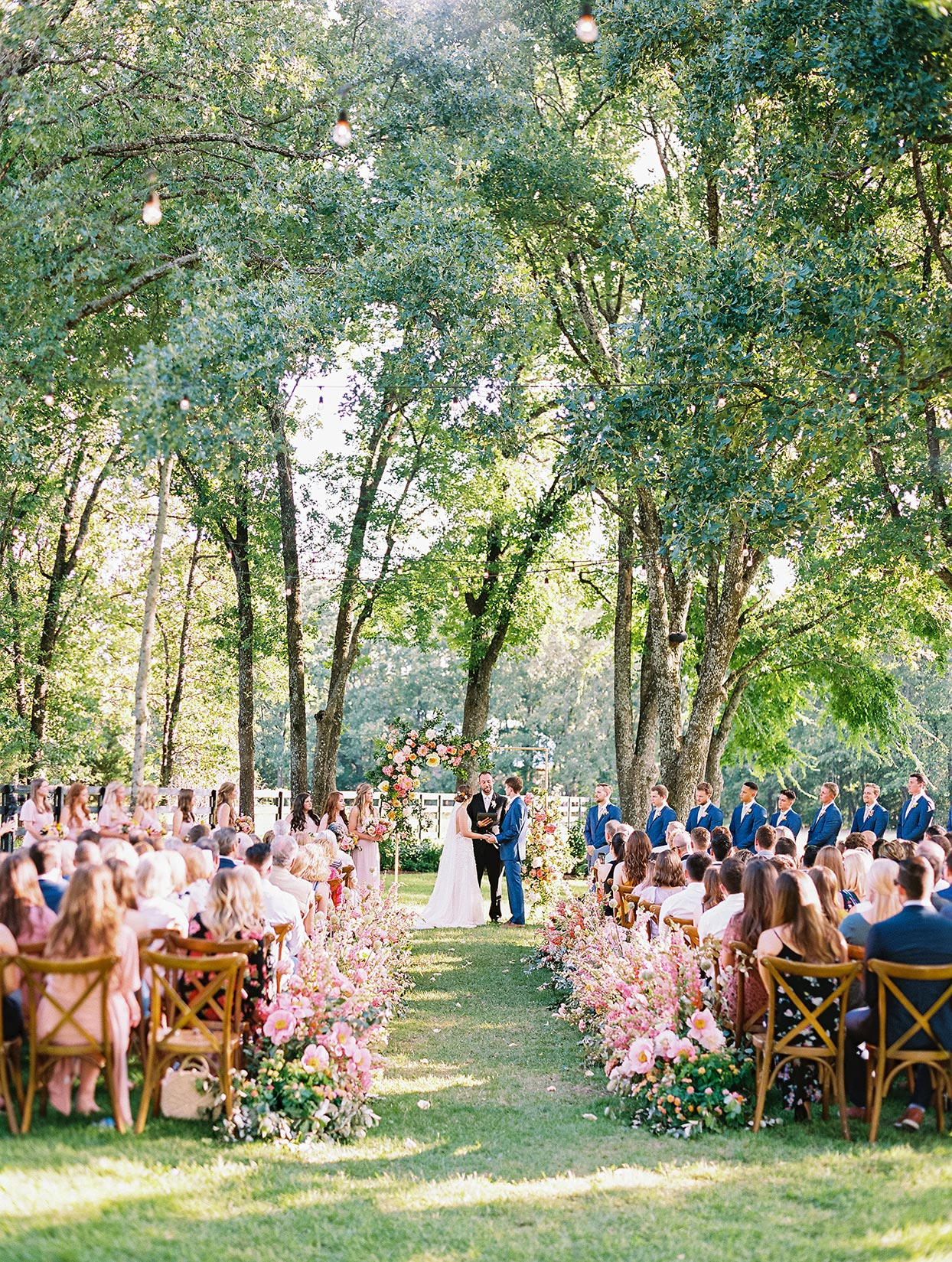 evie joe wedding ceremony guests in wooden chairs facing couple