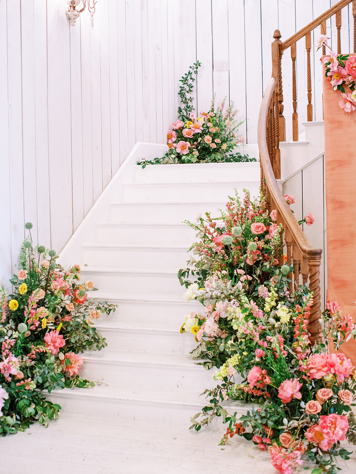 evie joe wedding reception white staircase with citrus colored florals