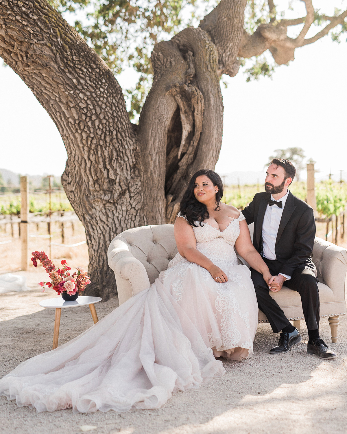 bride and groom outside sitting on cream colored couch