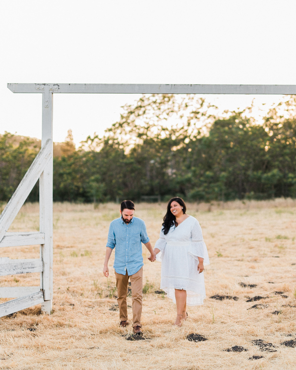 bride and groom under white painted wood archway