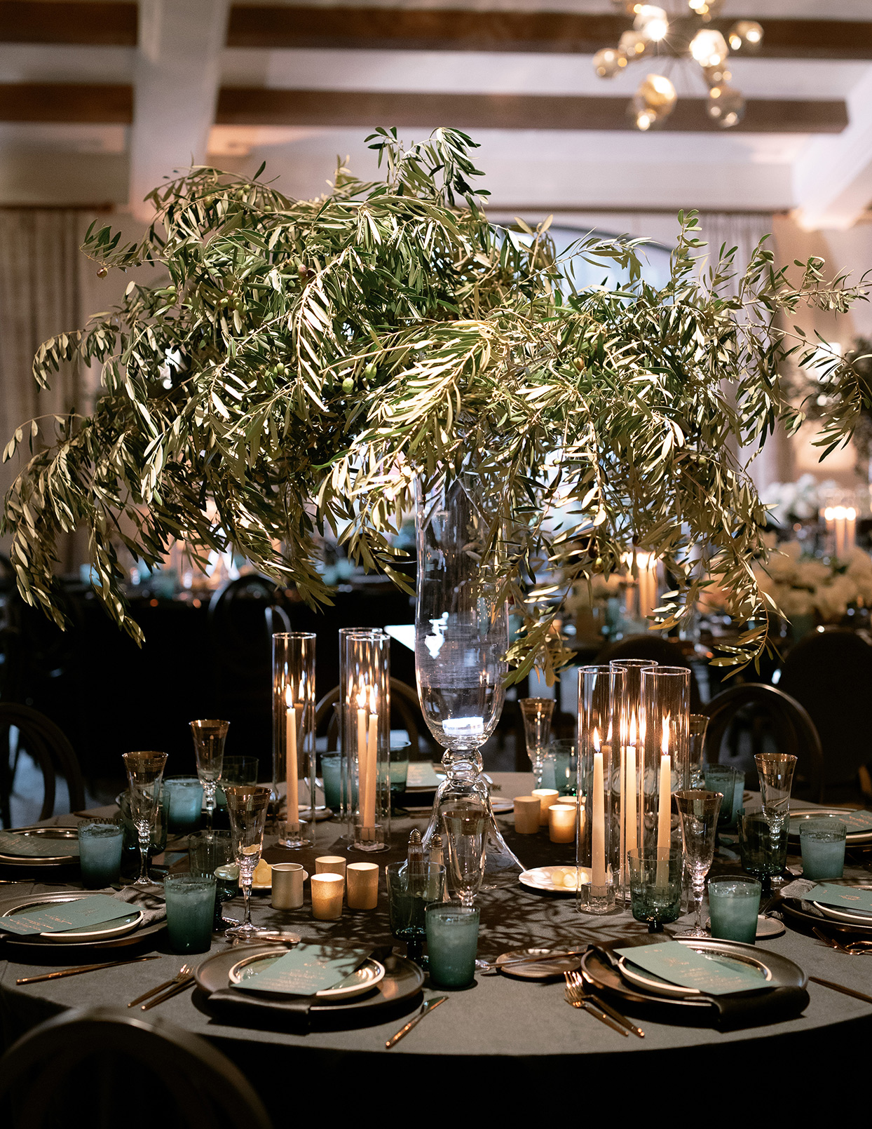 jason justin wedding reception dark tablescape with large greenery centerpiece