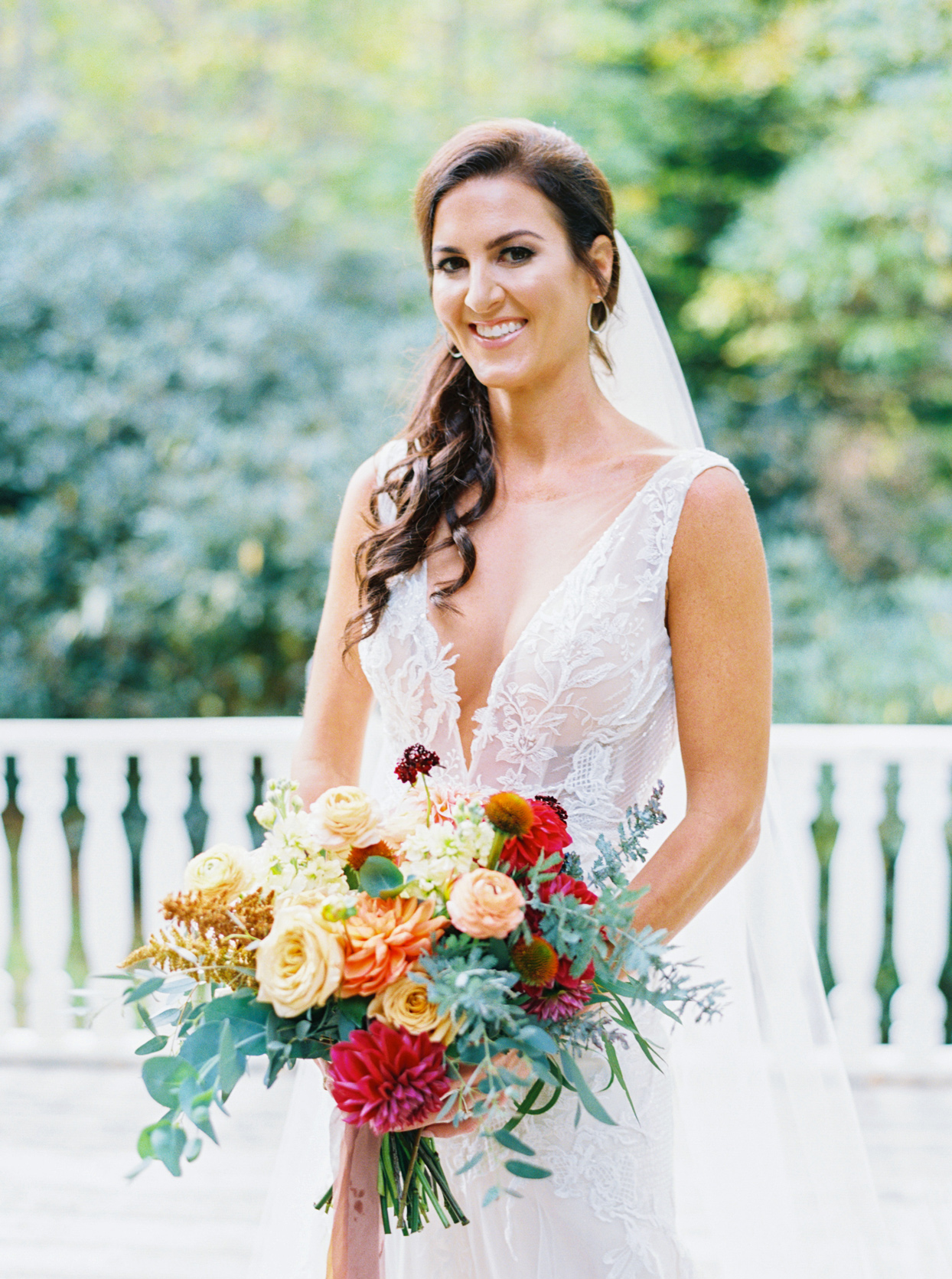 Bride wearing Adam Zohar gown with plunging v-neck, handmade lace, and fitted bodice