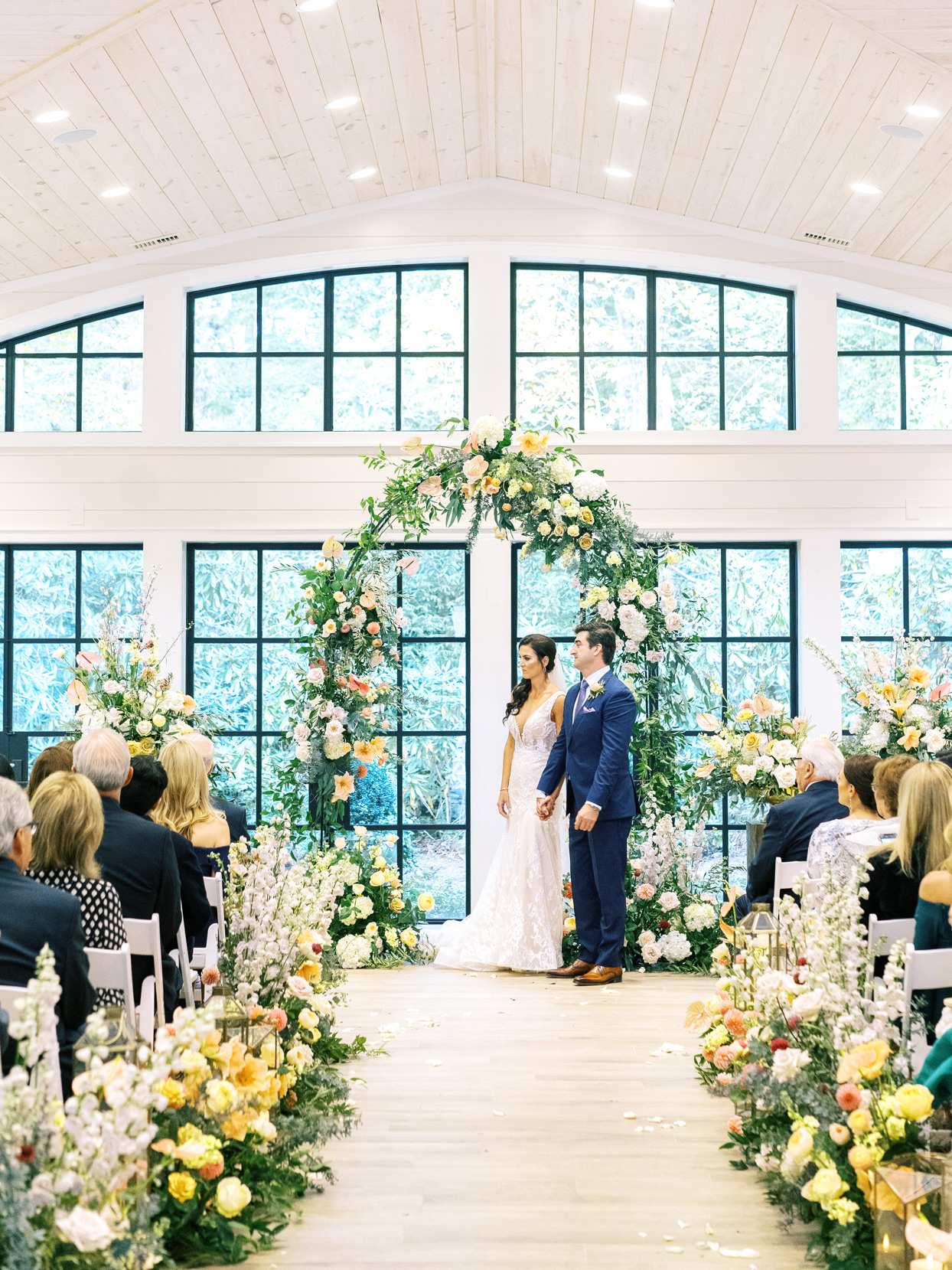 Bride and groom standing under floral arch during wedding ceremony