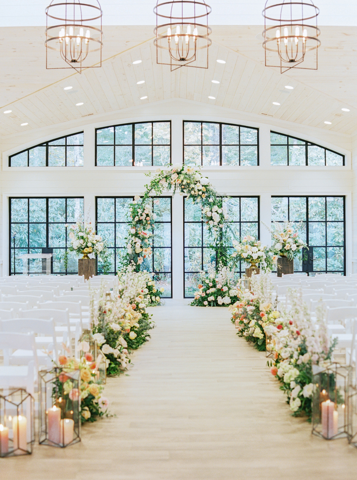 Orchard House with vaulted pine ceiling was accented with gold chandeliers and lanterns holding lit pillar candles along the aisle