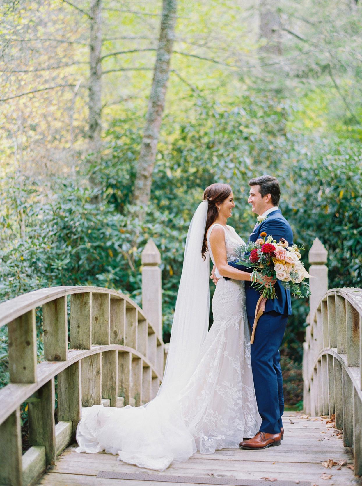Bride and groom standing together on bridge