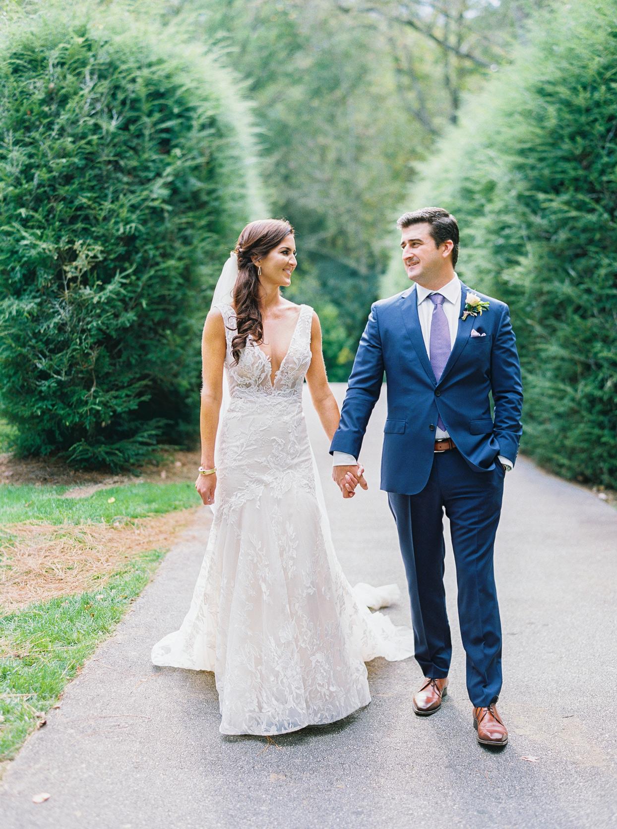 Bride and groom walking down sidewalk together