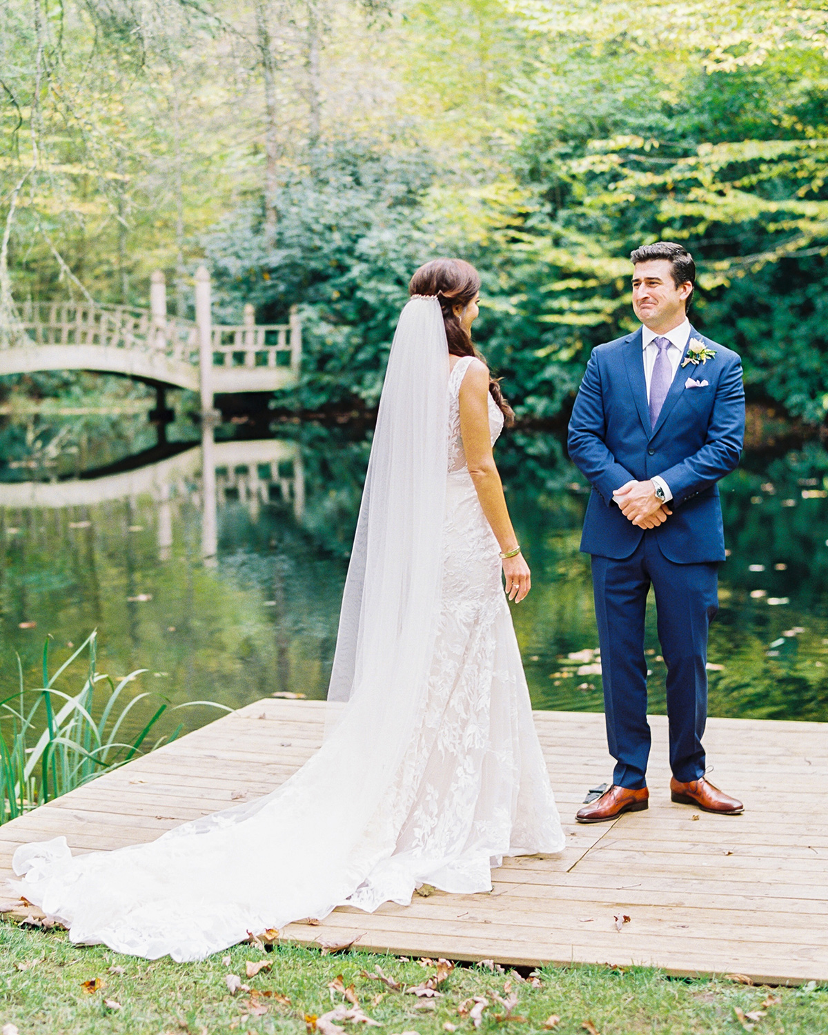 Bride and groom on wooden bridge during first look