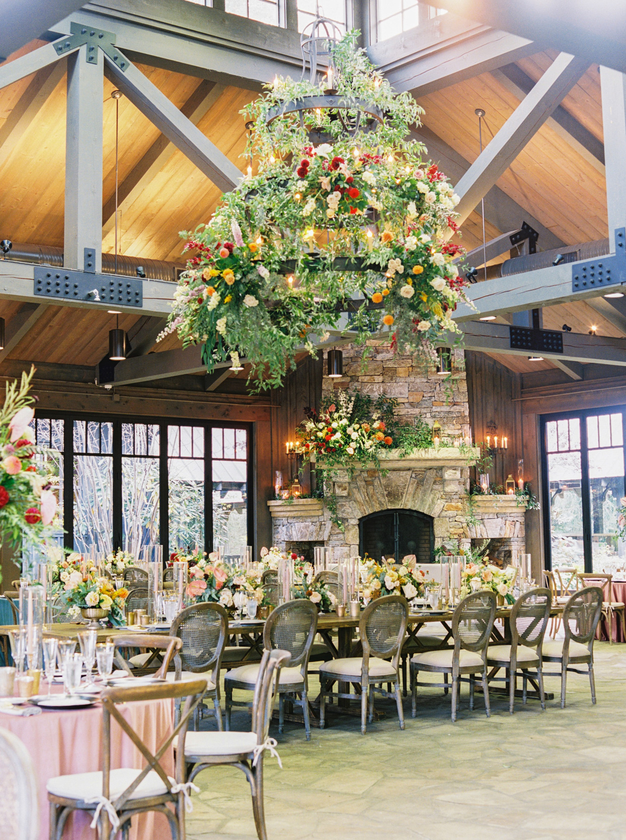 Indoor wedding reception in a wood-ceilinged room accented by tall windows and an elegant stone fireplace