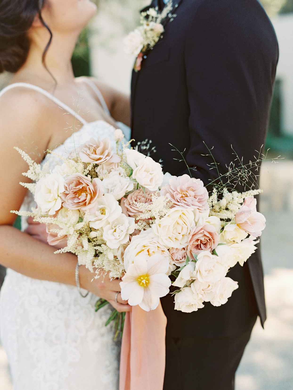 Bride holding a bouquet with Italian pit, explosion grass, garden spray roses, spray roses, garden roses, tulips, carnations, astilbe, and preserved florals