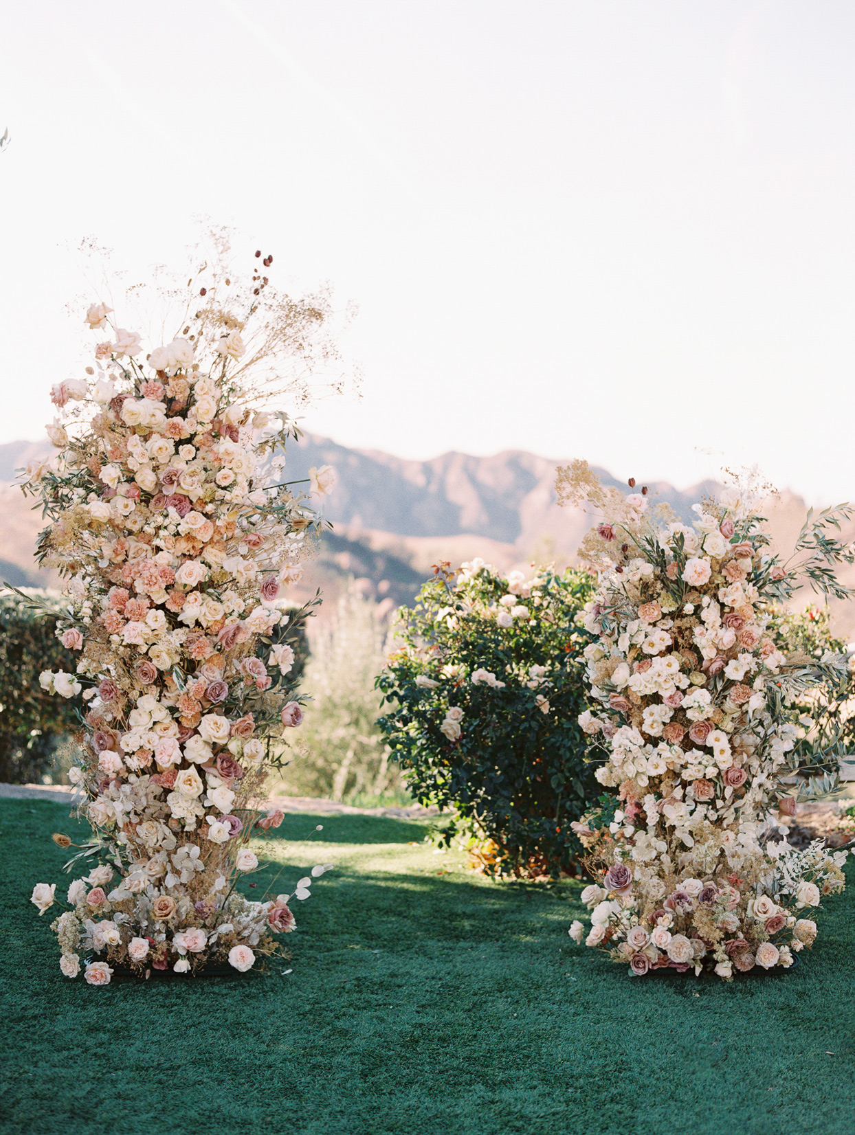 Ceremony structure of two posts built on wheels decorated with dried flowers in cream and pink tones