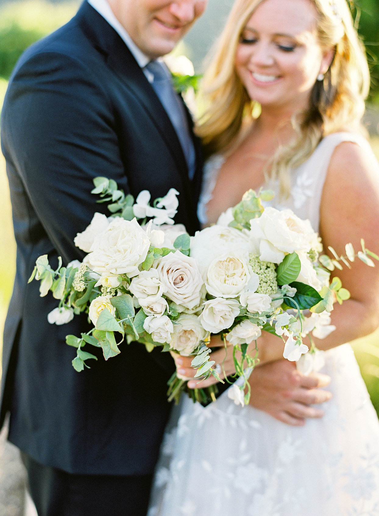 bride and groom smiling with wedding bouquet of neutral colored florals