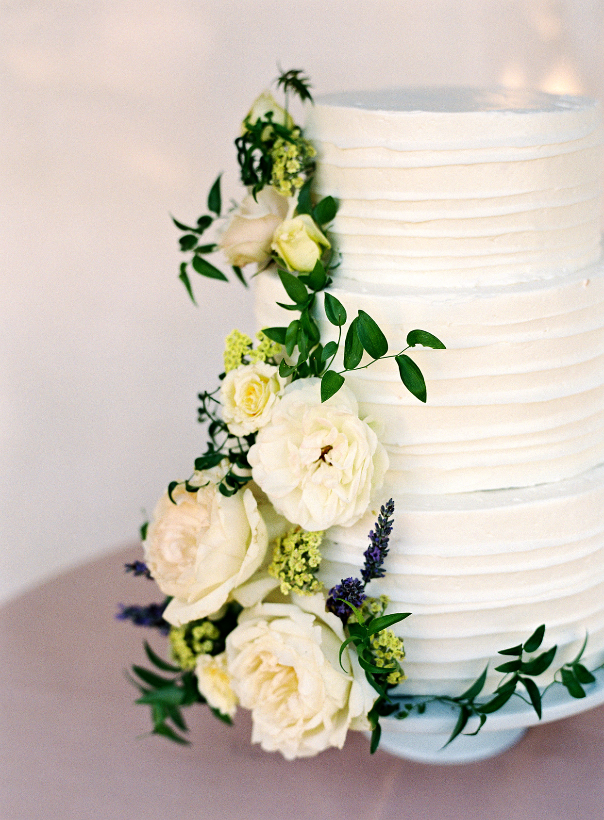 three tiered white frosted wedding cake with floral accent down the side
