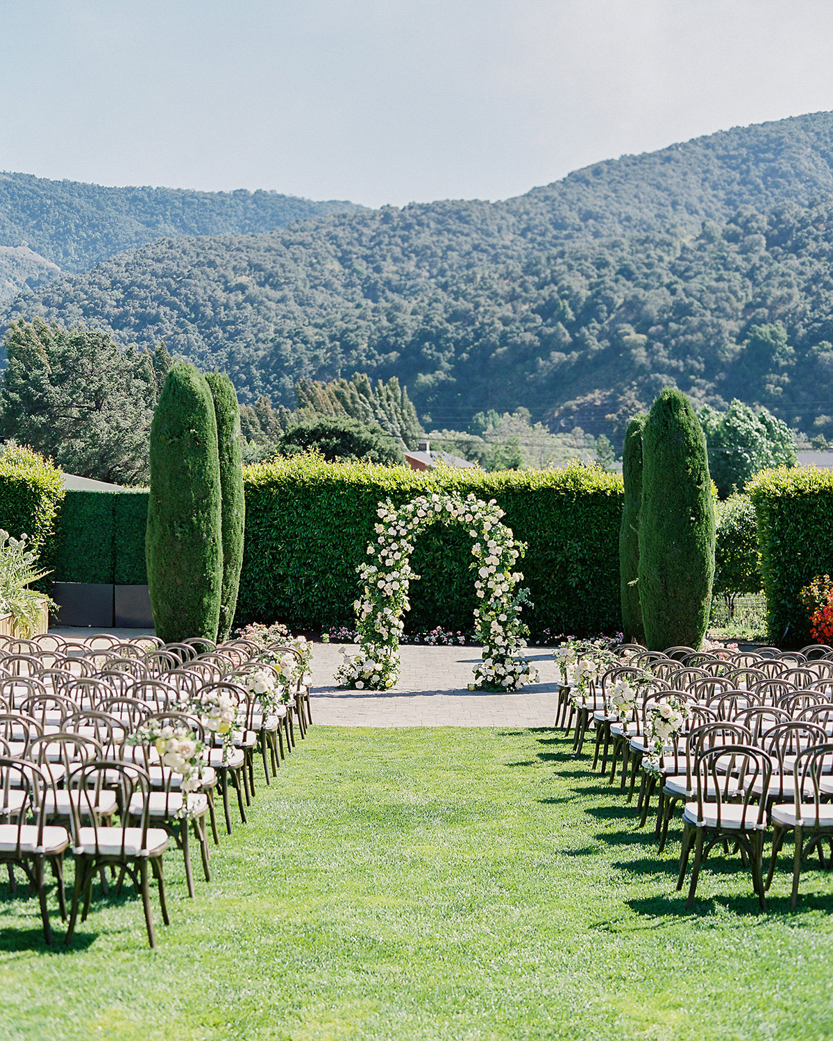 outdoor wedding ceremony seating and floral arch by green shrubs