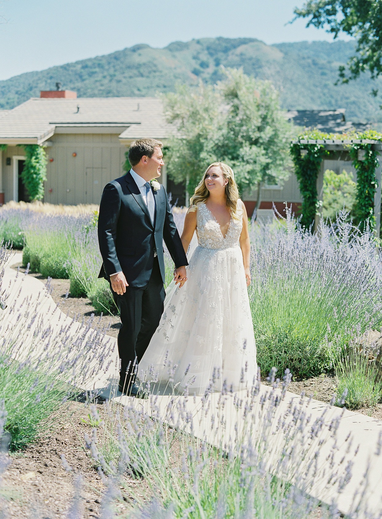 bride and groom holding hands outside by lavender garden