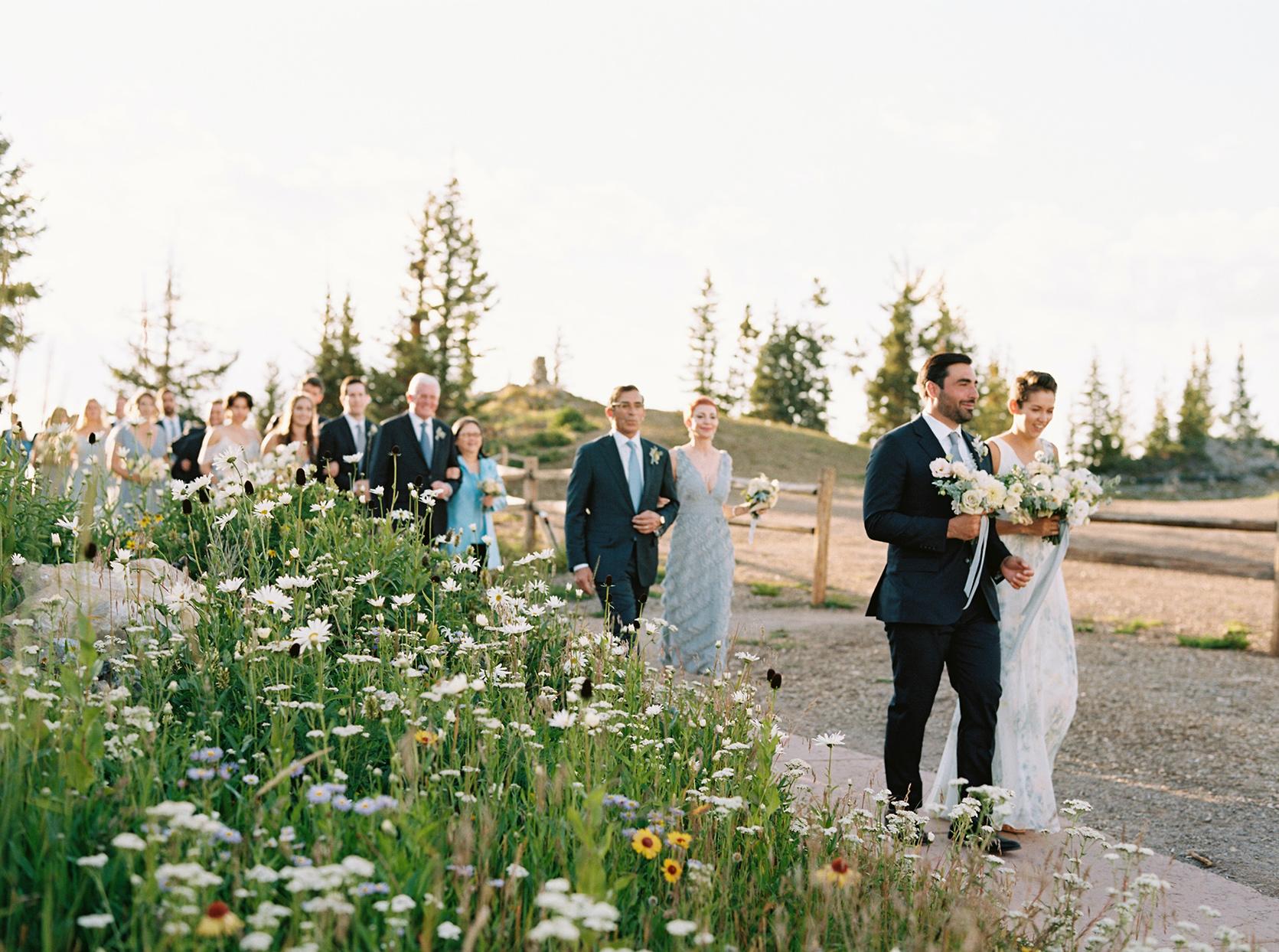 kimmie mike wedding guests walking by flower field
