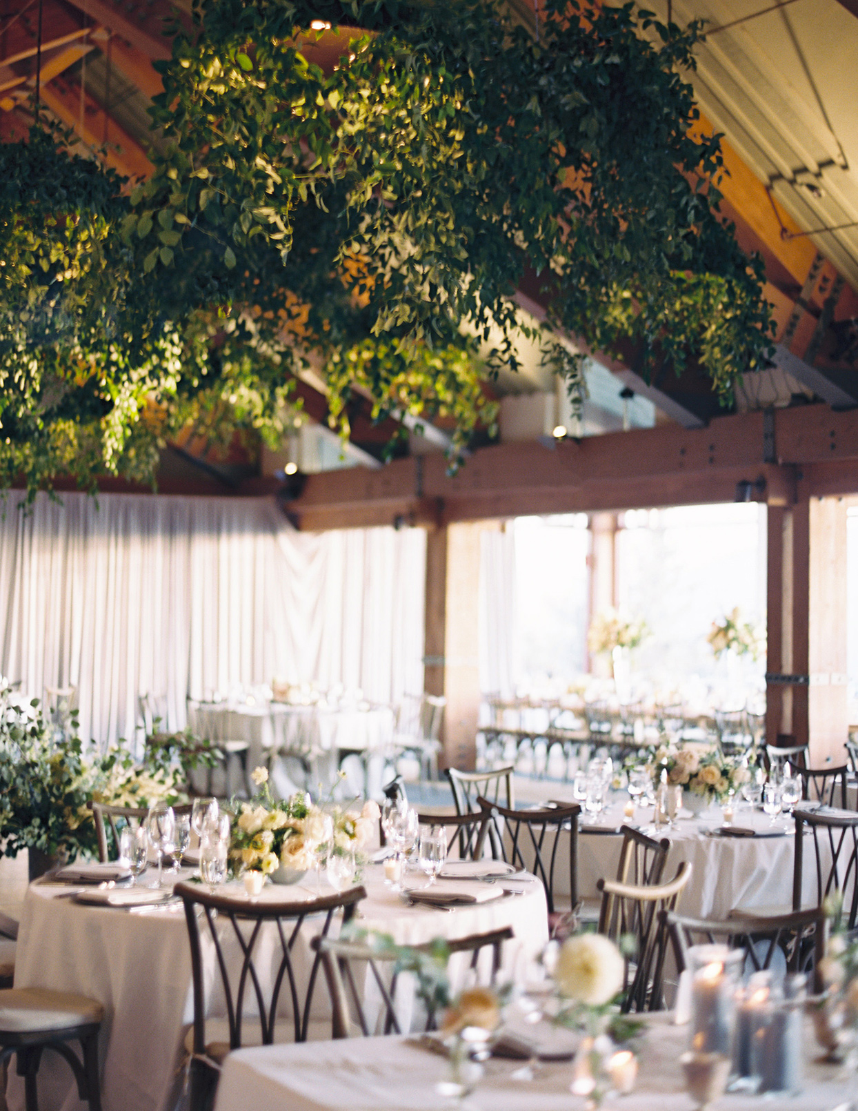 kimmie mike wedding reception space with greenery hanging from ceiling
