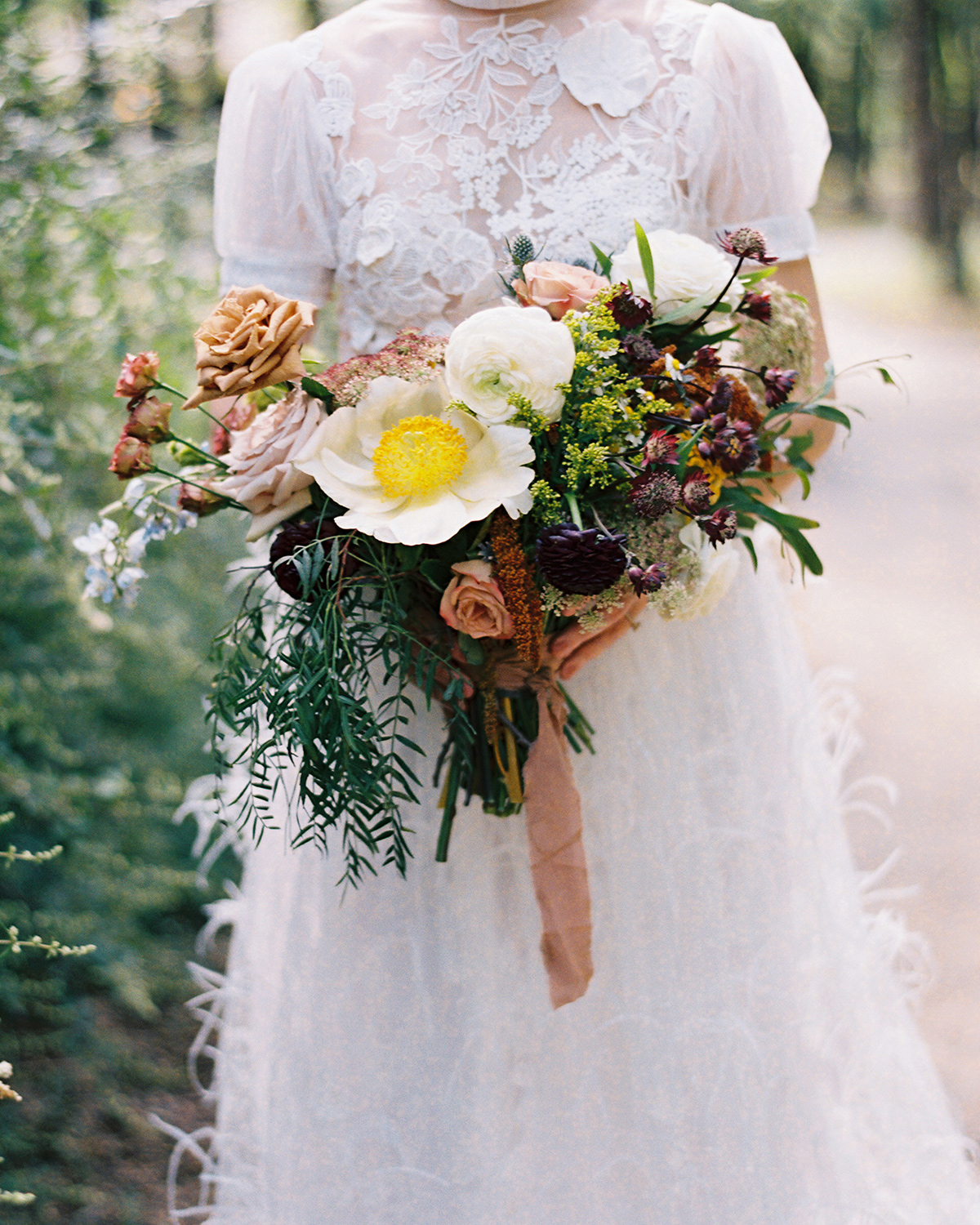Bride holding bouquet of colorful wildflowers