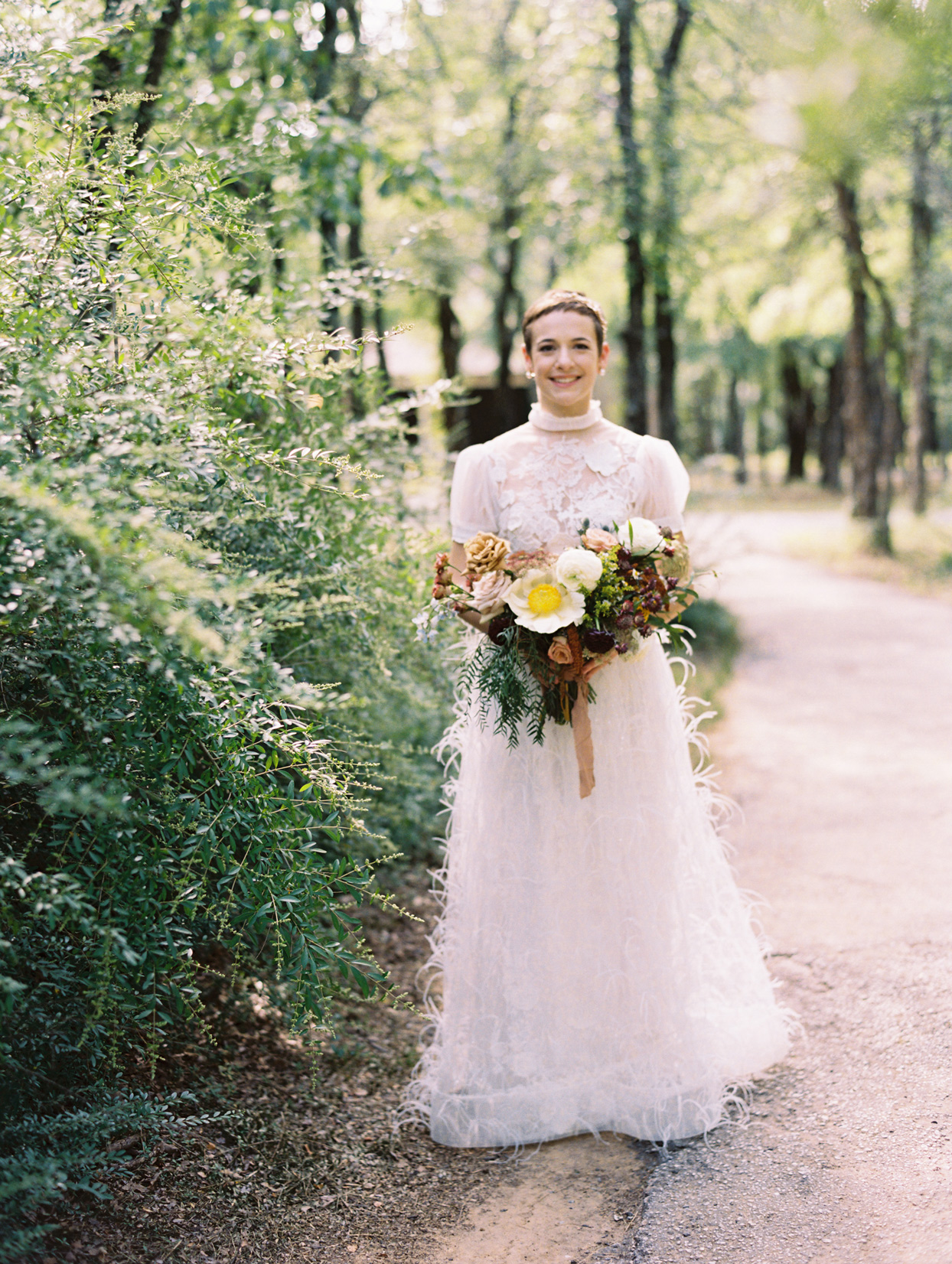 Bride in sheer, lacy gown with a high neck and puffed sleeves, and a feather-covered skirt