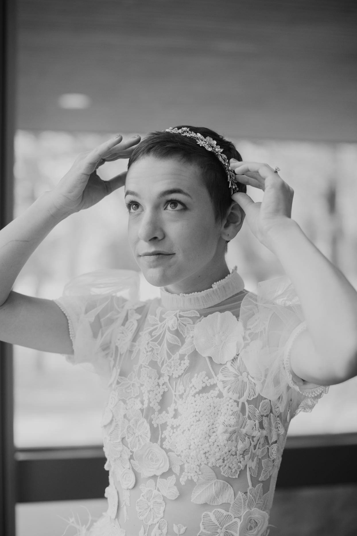 Bride placing a simple jeweled headband on her head