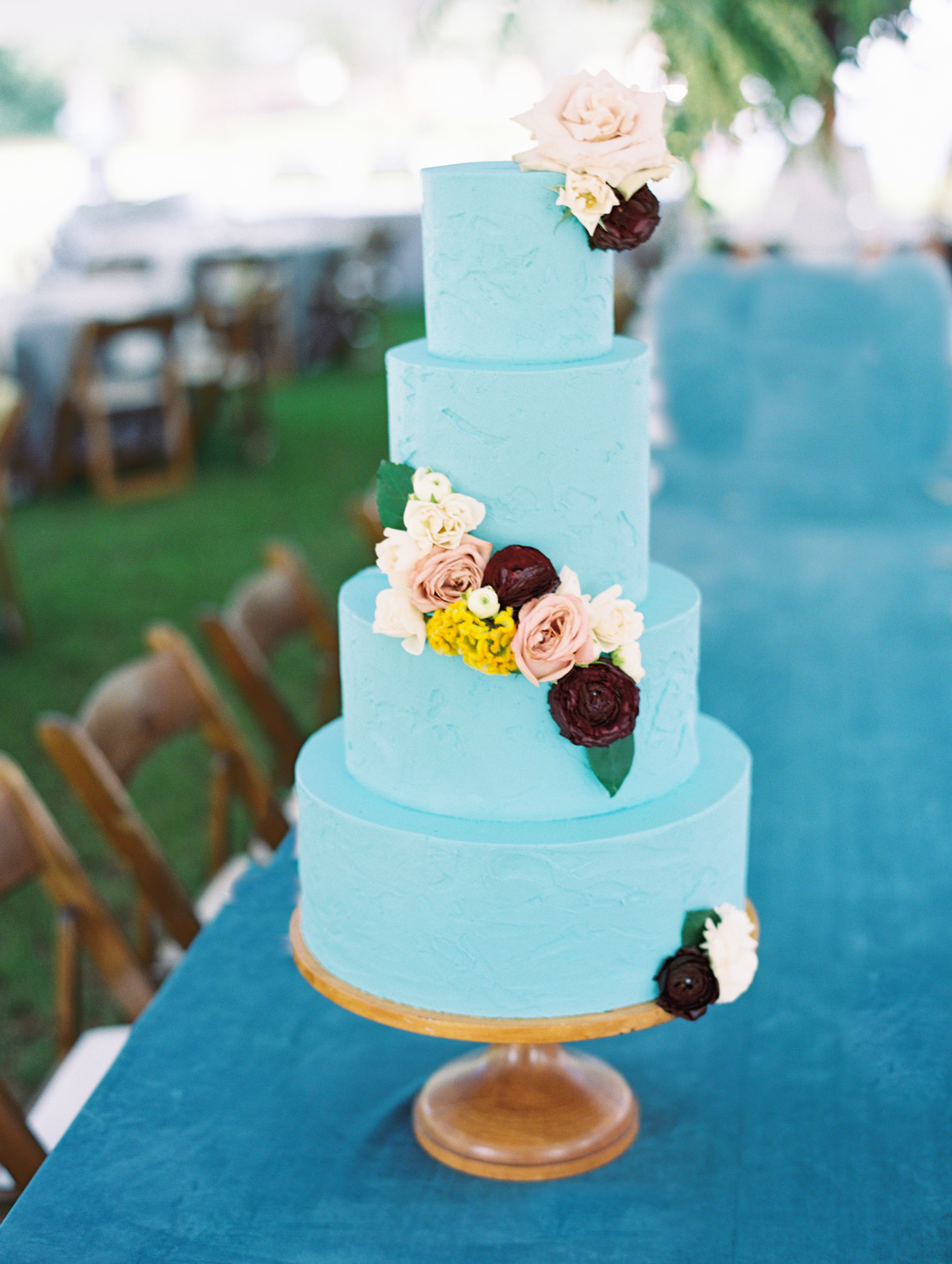 Four tiered blue wedding cake with flowers